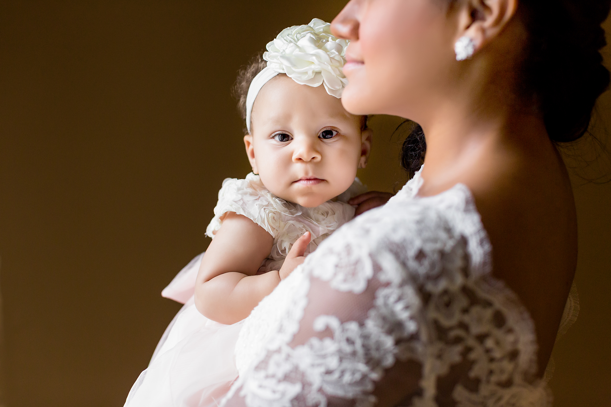 Bride holding dressed up baby girl - photo by Procopio Photography