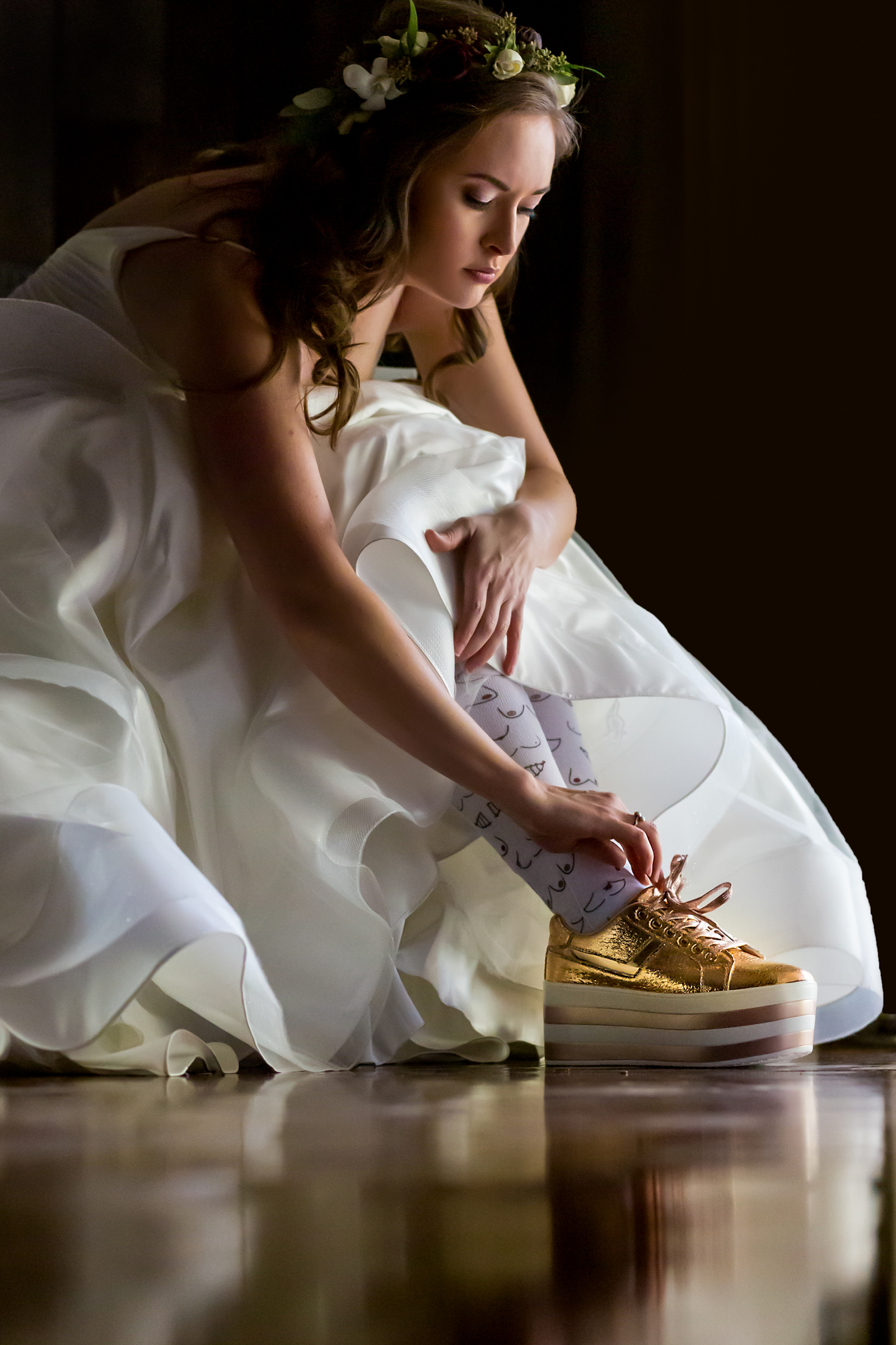 Bride putting on sparkly gold platform sneakers - photo by Procopio Photography