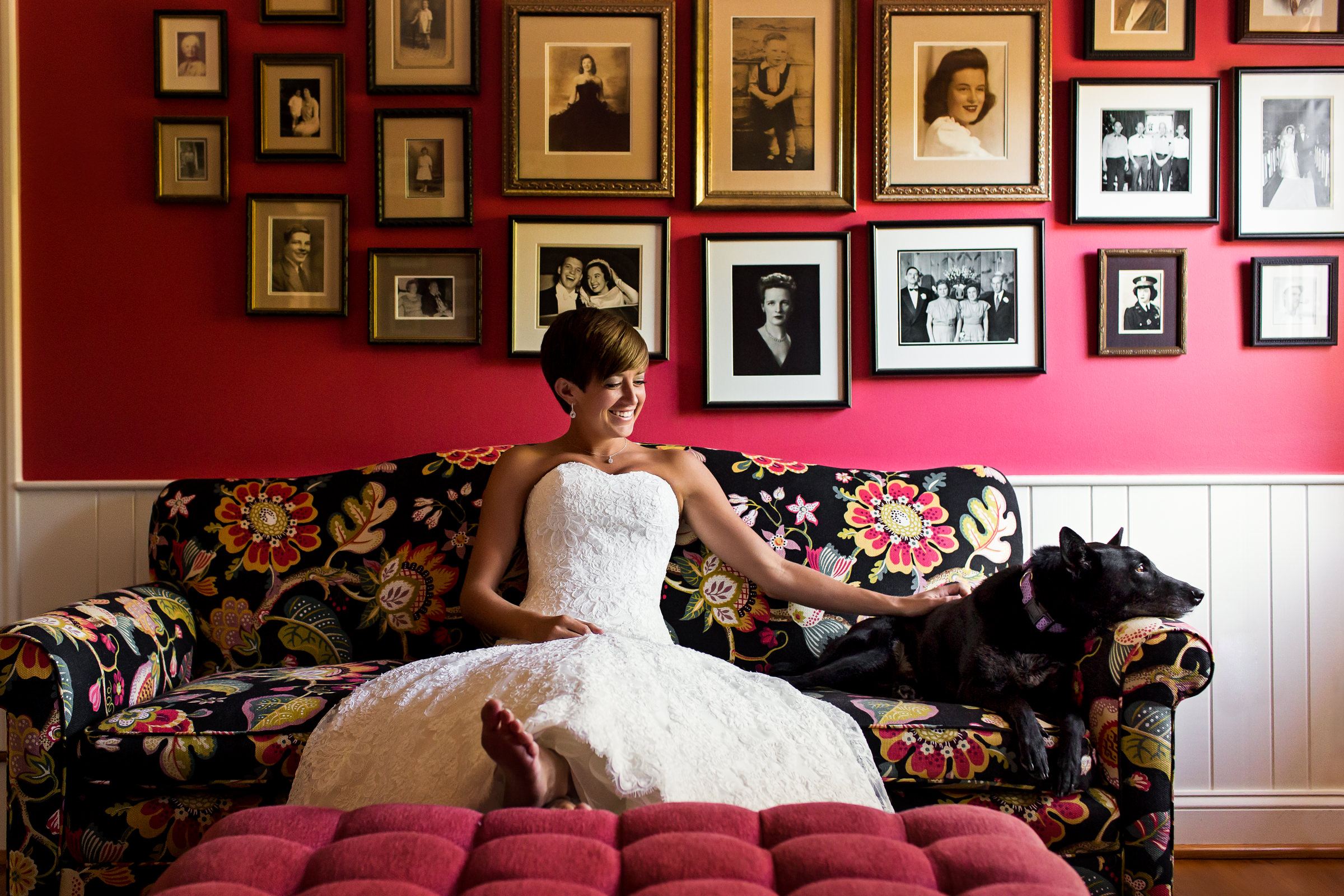 Bride with dog on floral couch against red wall covered in photos - photo by Procopio Photography
