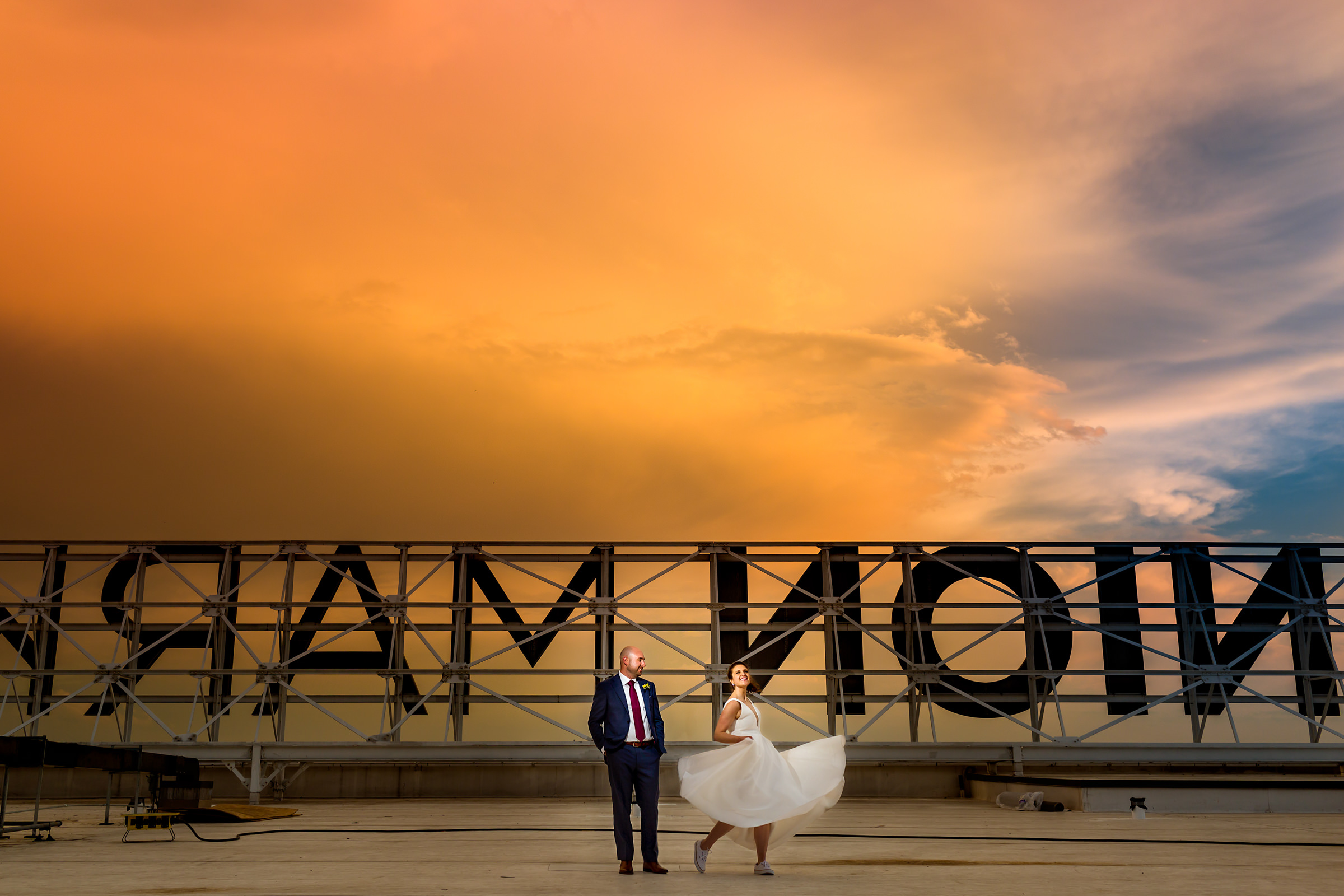 Couple against huge outdoor sign at sunset - photo by Procopio Photography