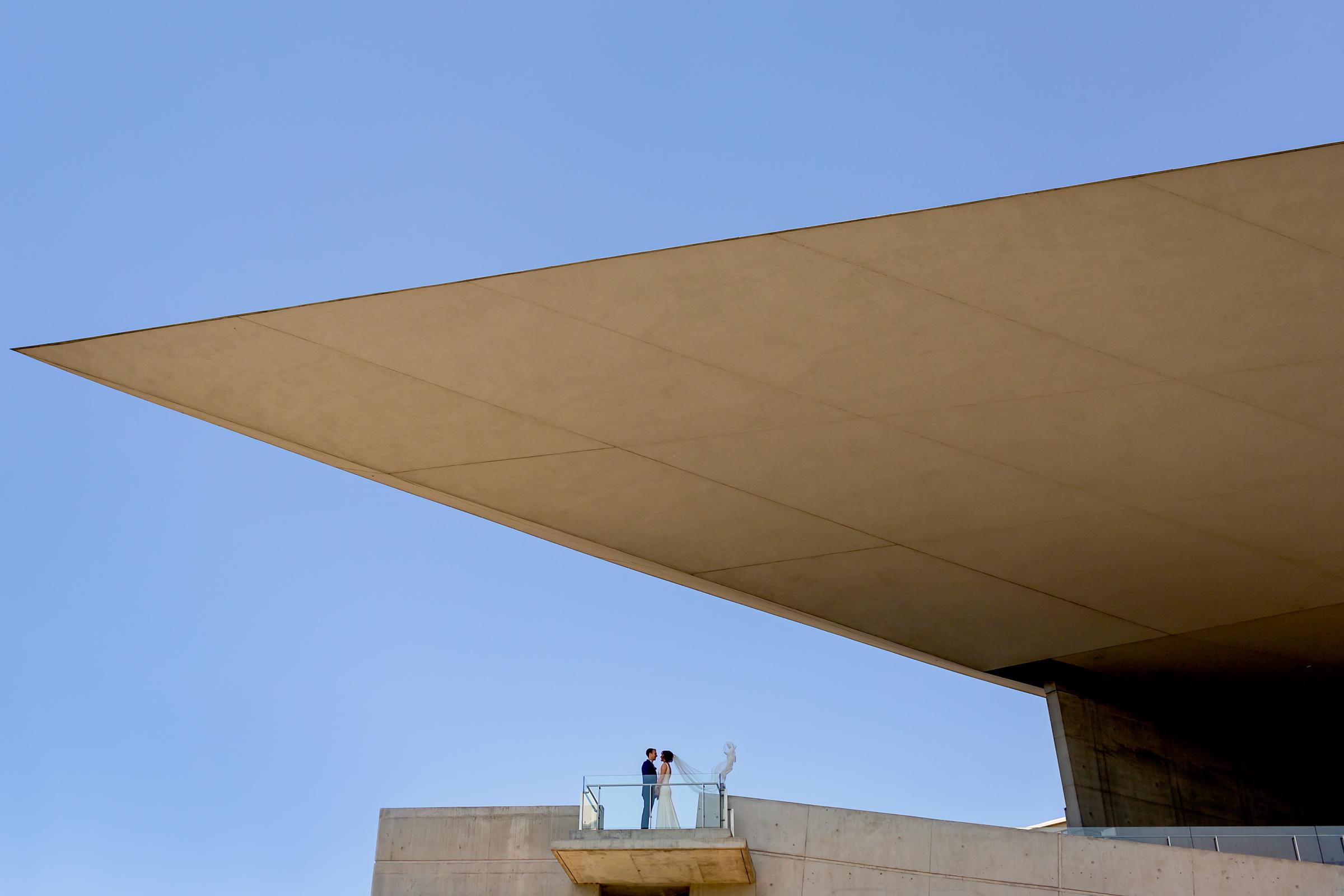 Couple landscape portrait against stark geometric arena stage - photo by Procopio Photography