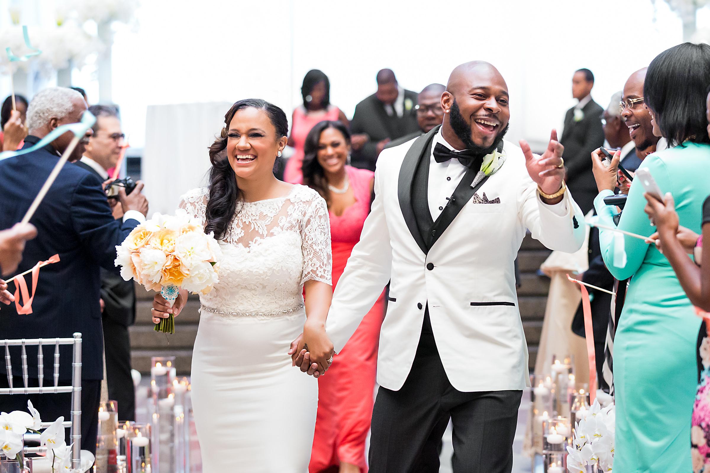 Happy couple walking up the aisle - photo by Procopio Photography