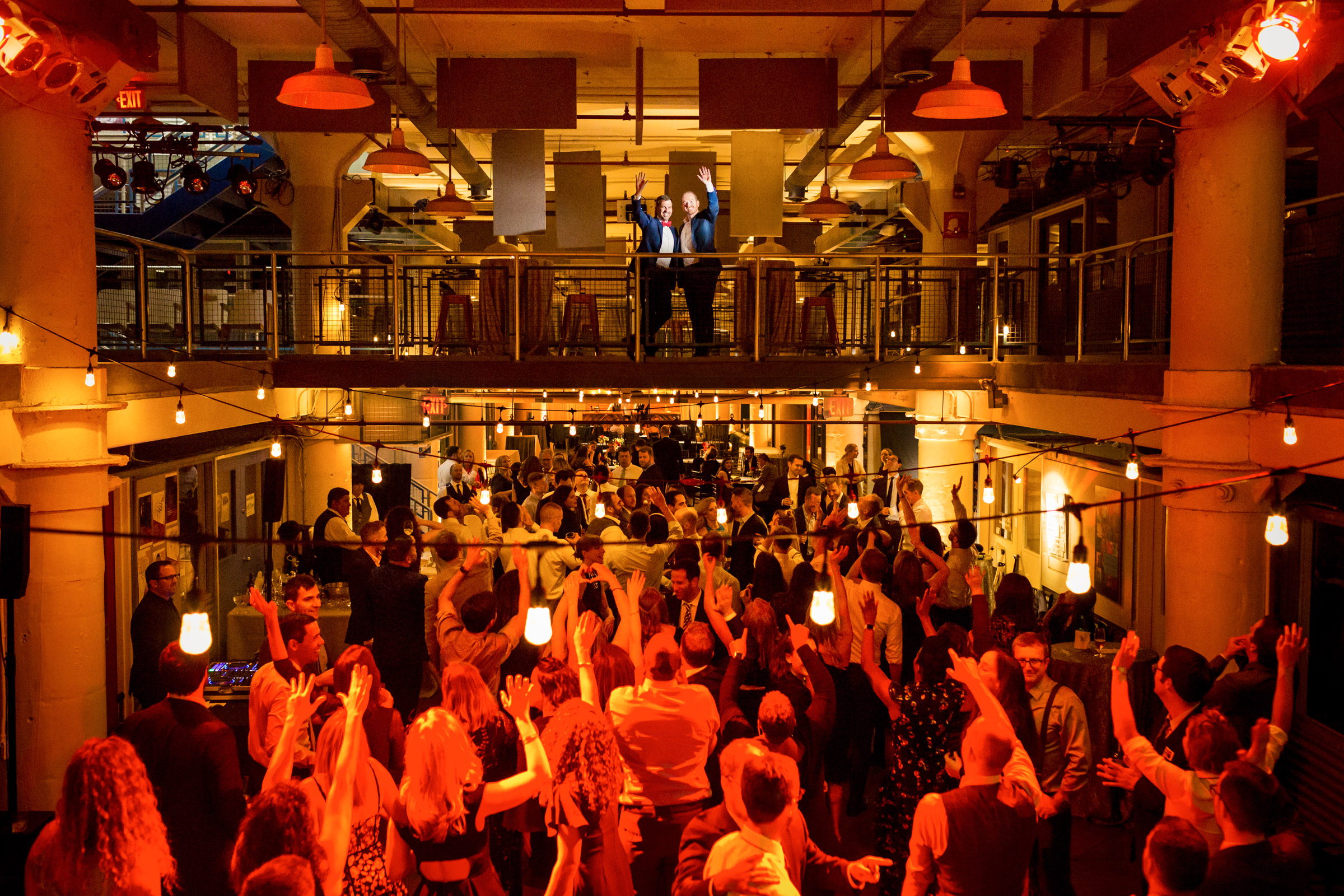Creative composition grooms on balcony wave to partiers below - photo by Procopio Photography
