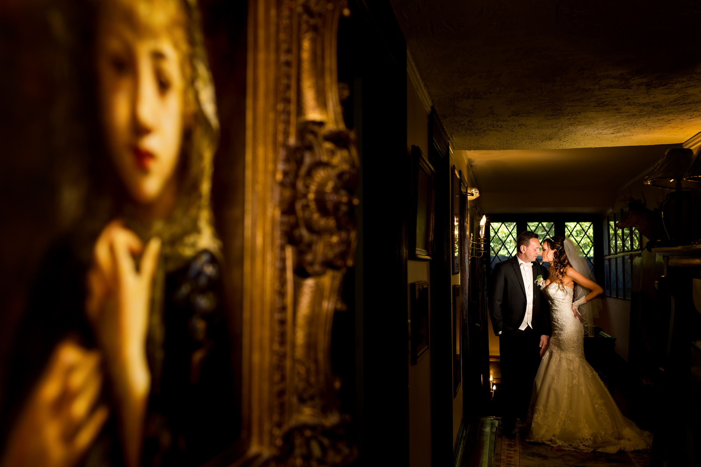 Dramatic light couple  portrait against paintings in gallery - photo by Procopio Photography