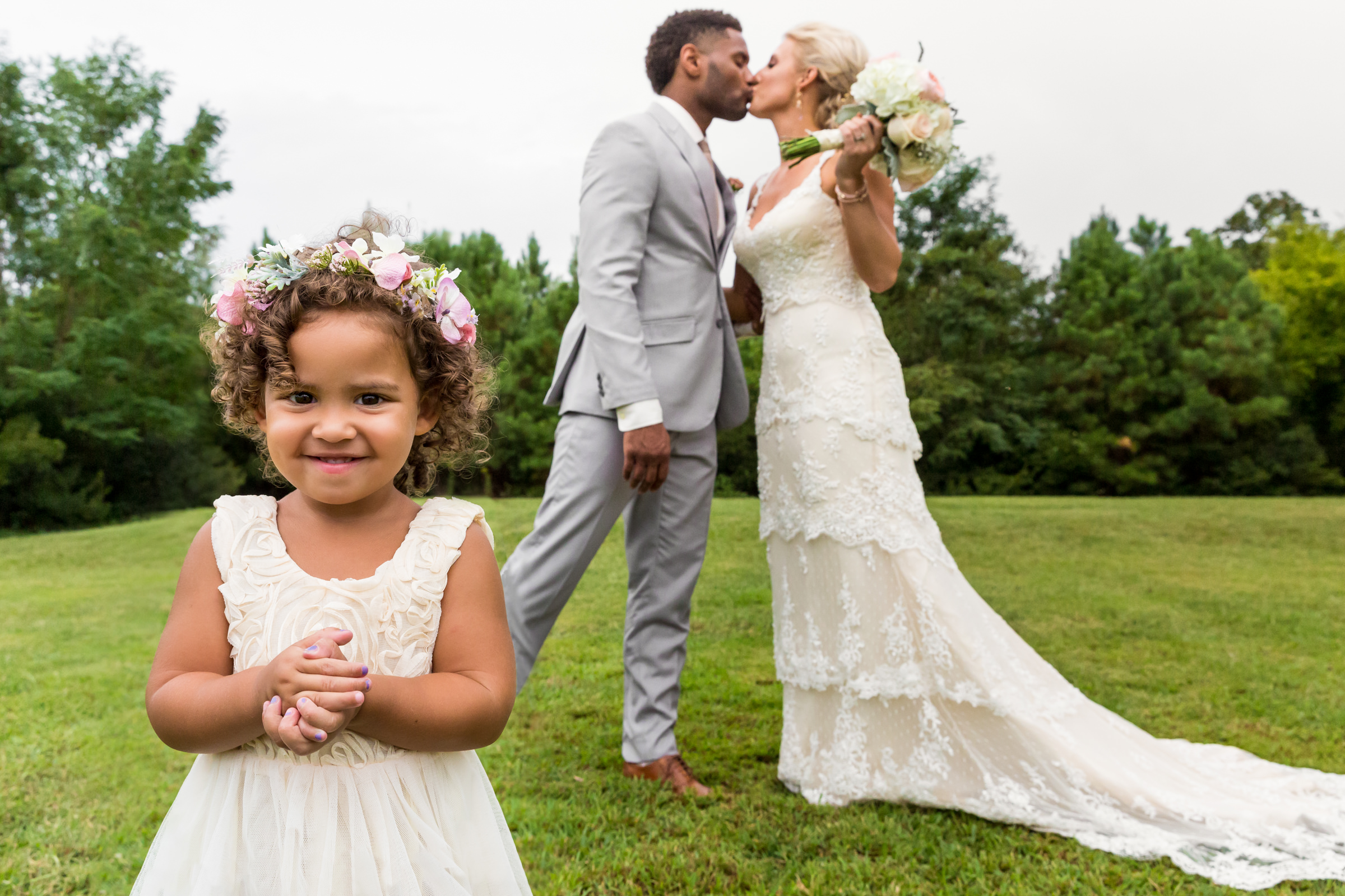Flower girl with kissing couple on lawn - photo by Procopio Photography