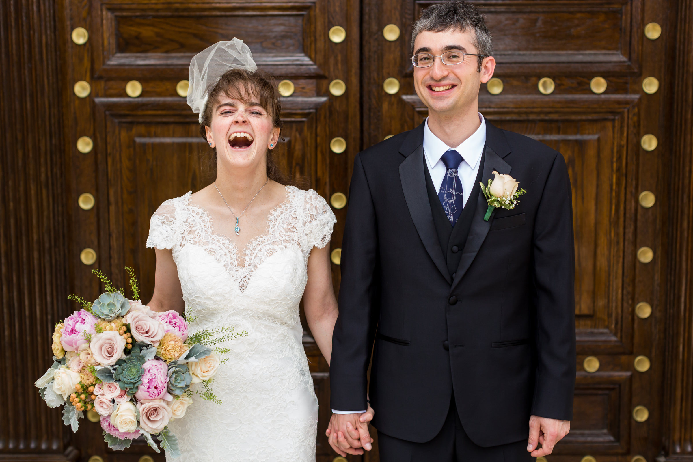 Laughing bride with groom against ornate wooden door - photo by Procopio Photography