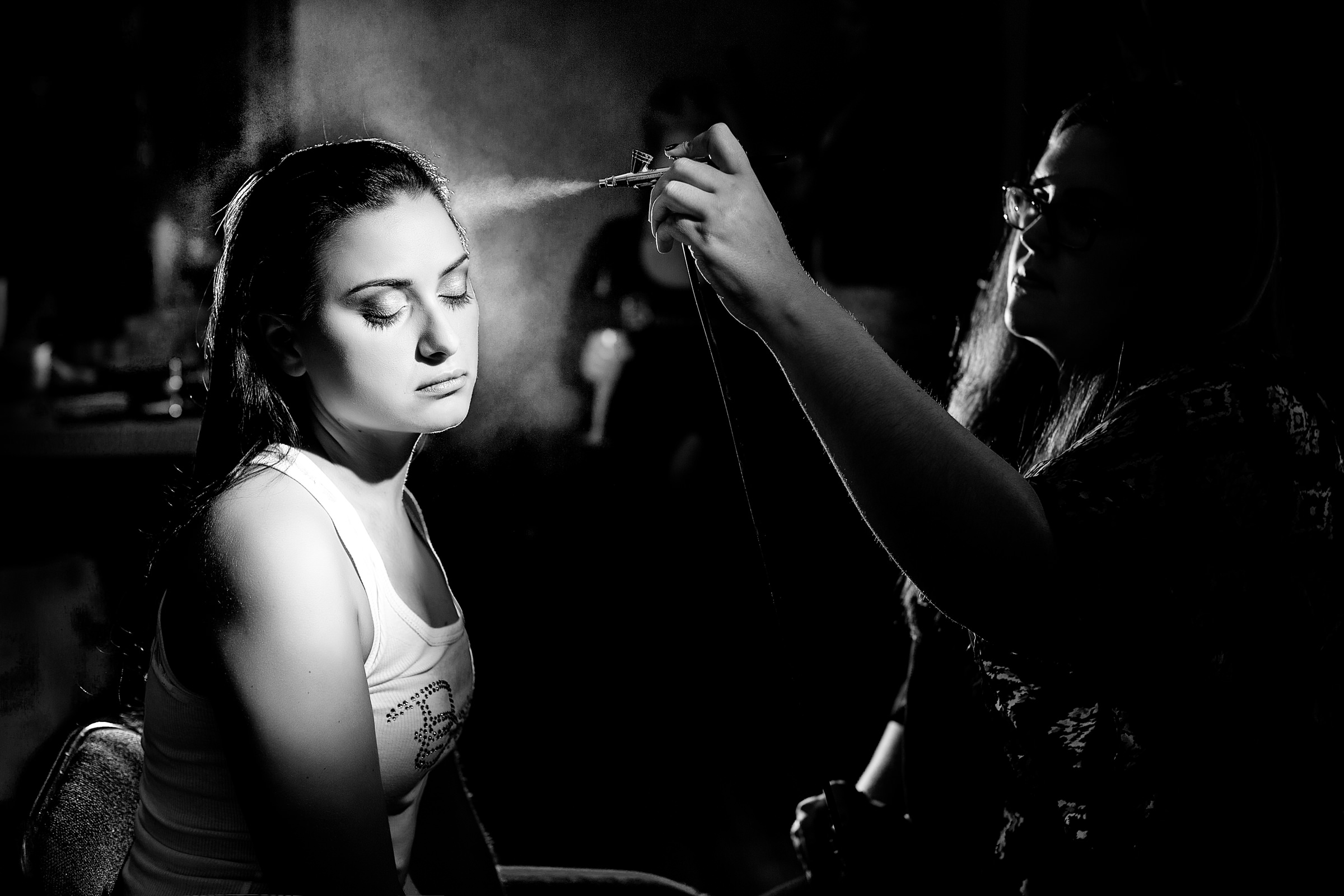 Makeup artist applies hairspray to bride in pin light - photo by Procopio Photography