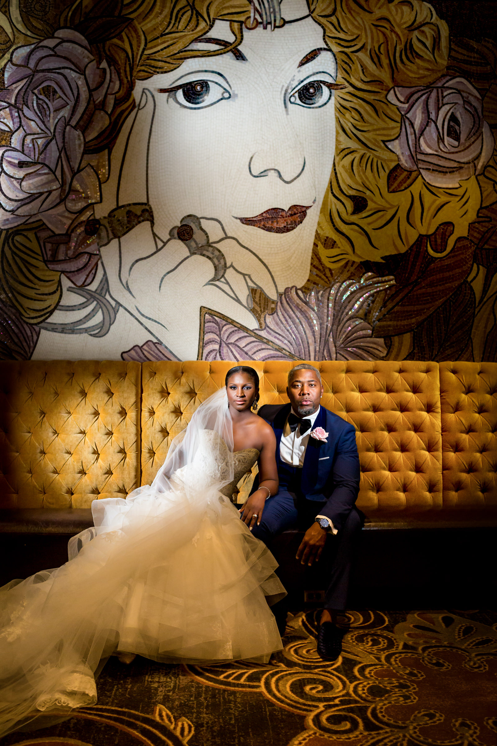 Seated couple portrait under striking mural - photo by Procopio Photography