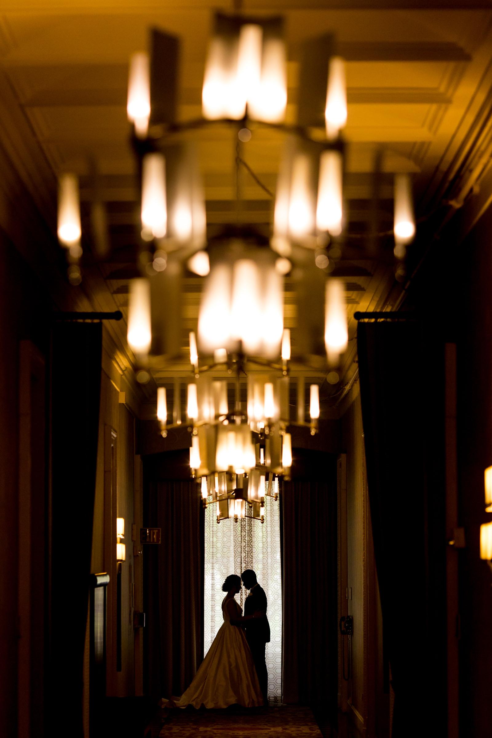 Silhouette couple portrait against chandeliers - photo by Procopio Photography