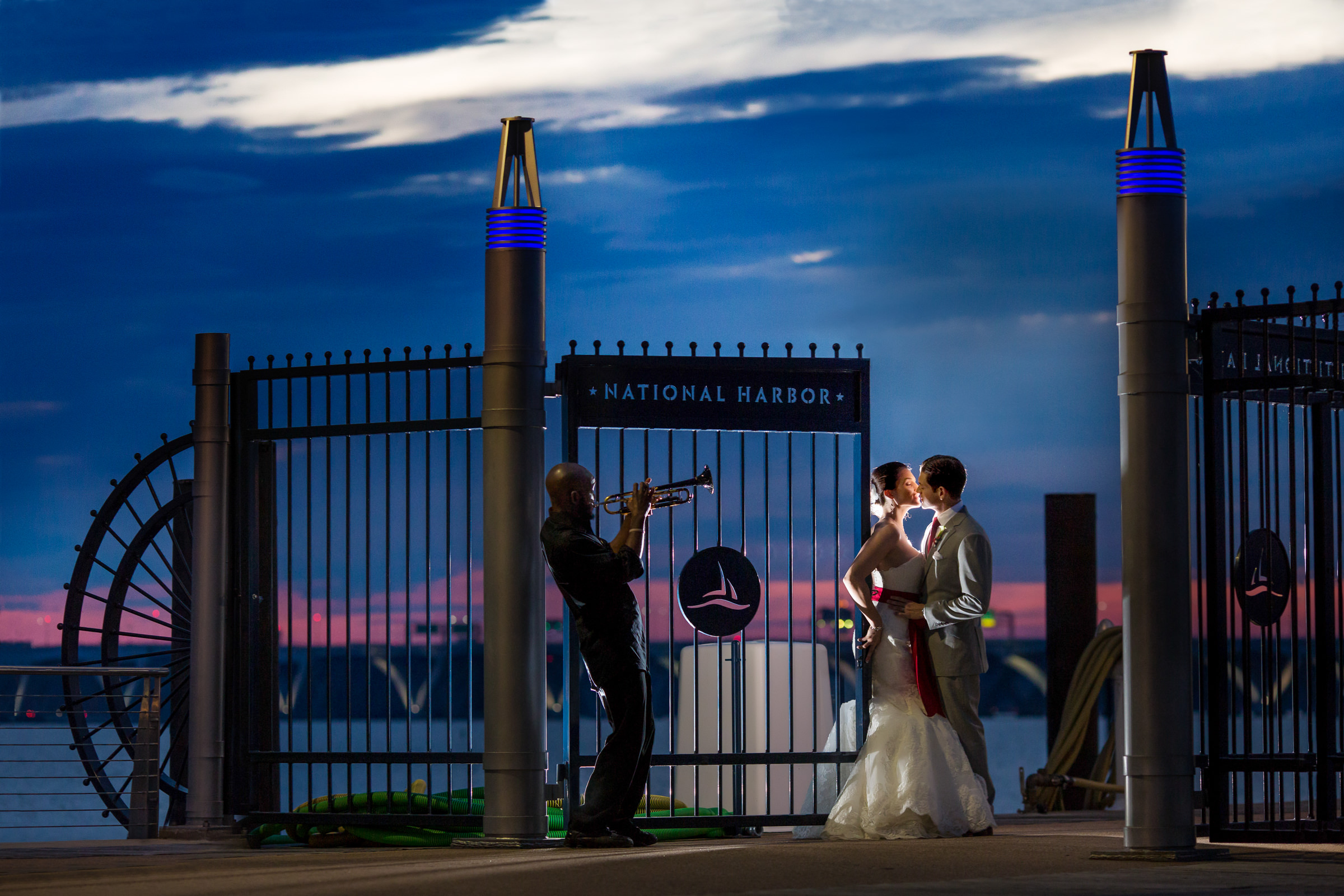 Trumpeter serenades couple at national harbor gate at sunset  - photo by Procopio Photography