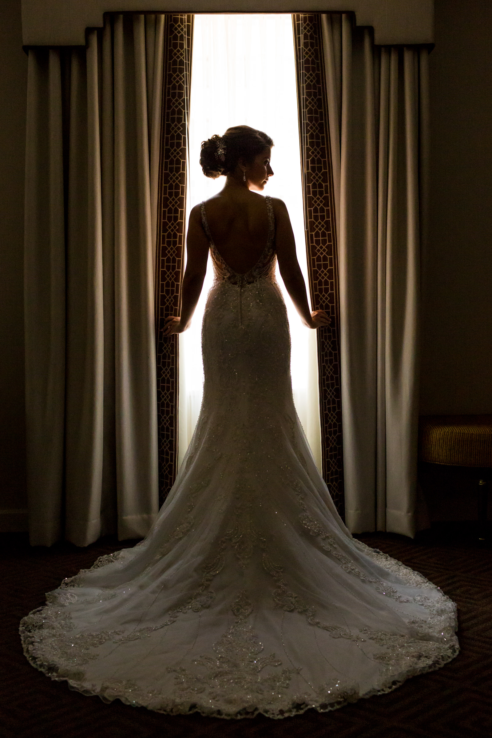 WIndow lit backview of bride with flowing train - photo by Procopio Photography