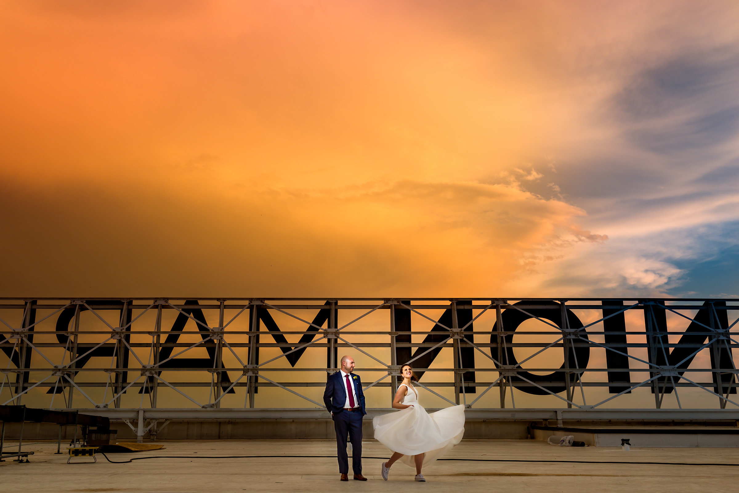 Couple against epic sunset sky and large lettering - photo by Procopio Photography