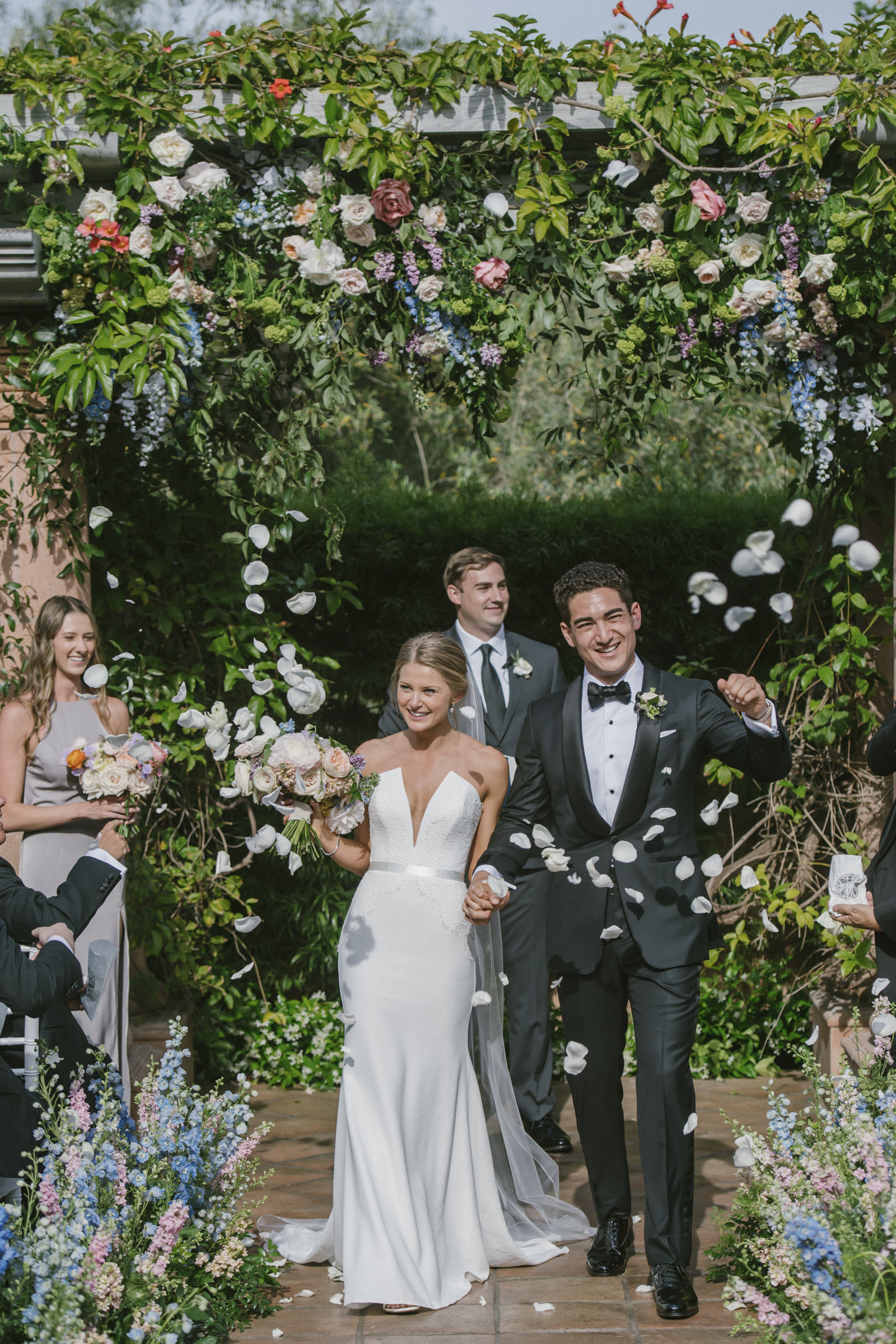 Bride and groom walk in floral aisle - photo by Amy and Stuart Photography