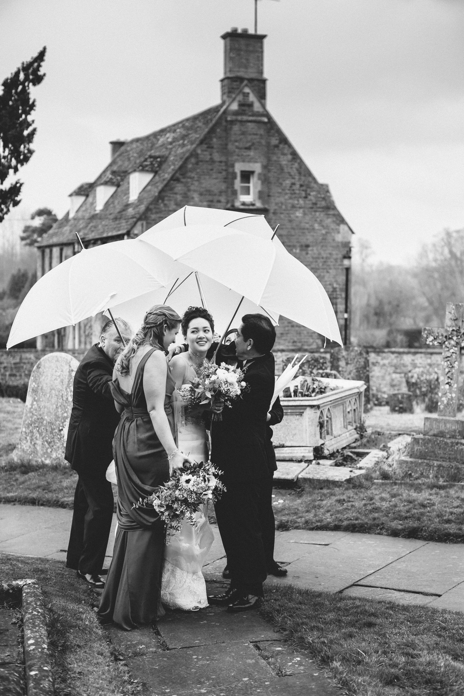 Bride and others under triad of white umbrellas - photo by Amy and Stuart Photography
