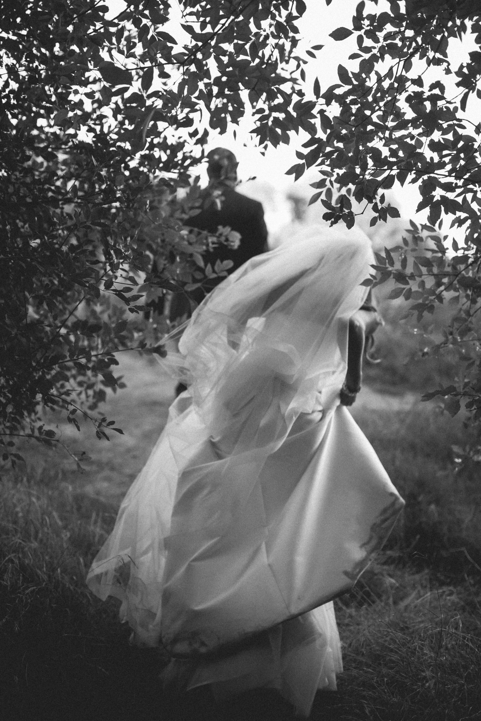 Bride running among trees - photo by Amy and Stuart Photography