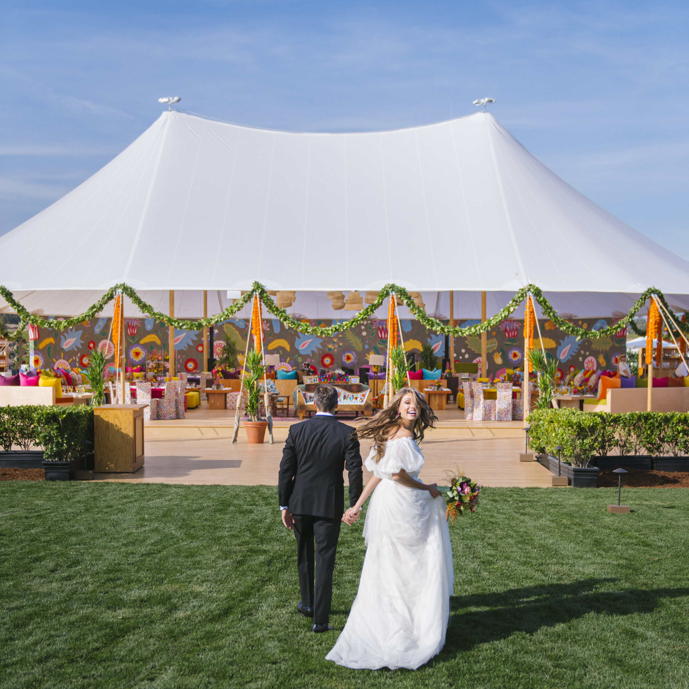 Couple walks toward tent with whimsical backdrop - photo by Amy and Stuart Photography