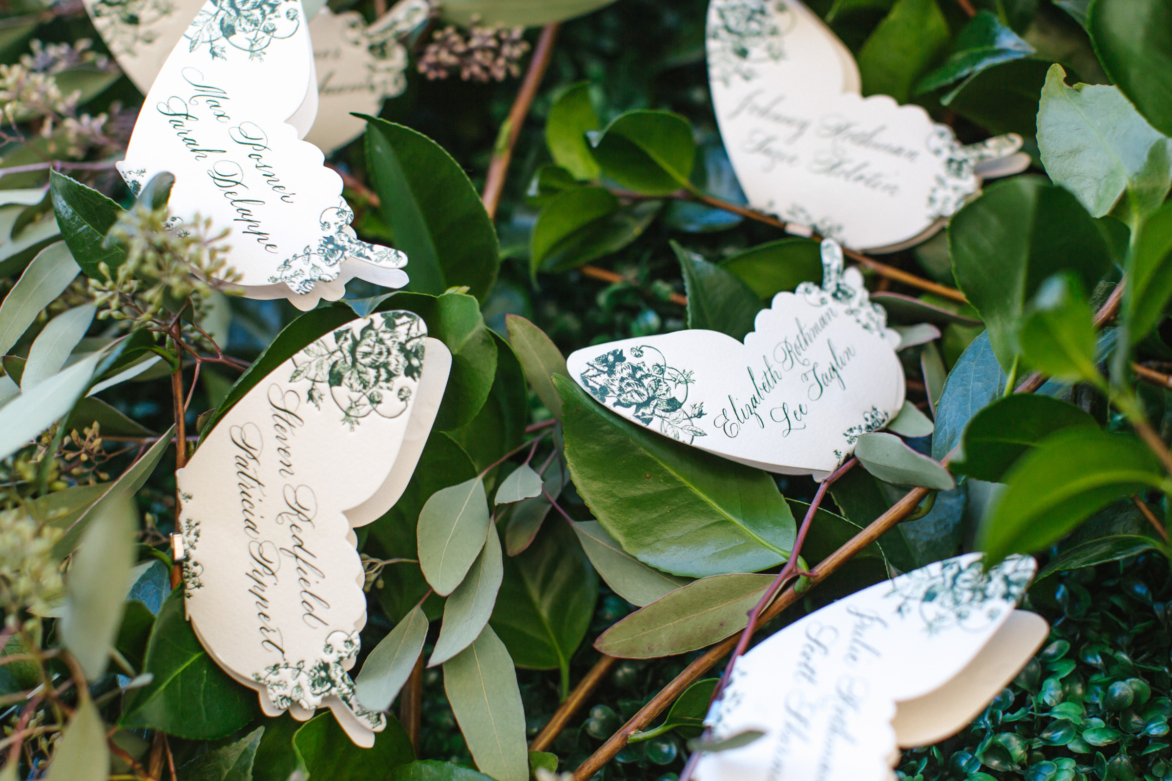 Butterfly shaped placards displayed in foliage - photo by Amy and Stuart Photography