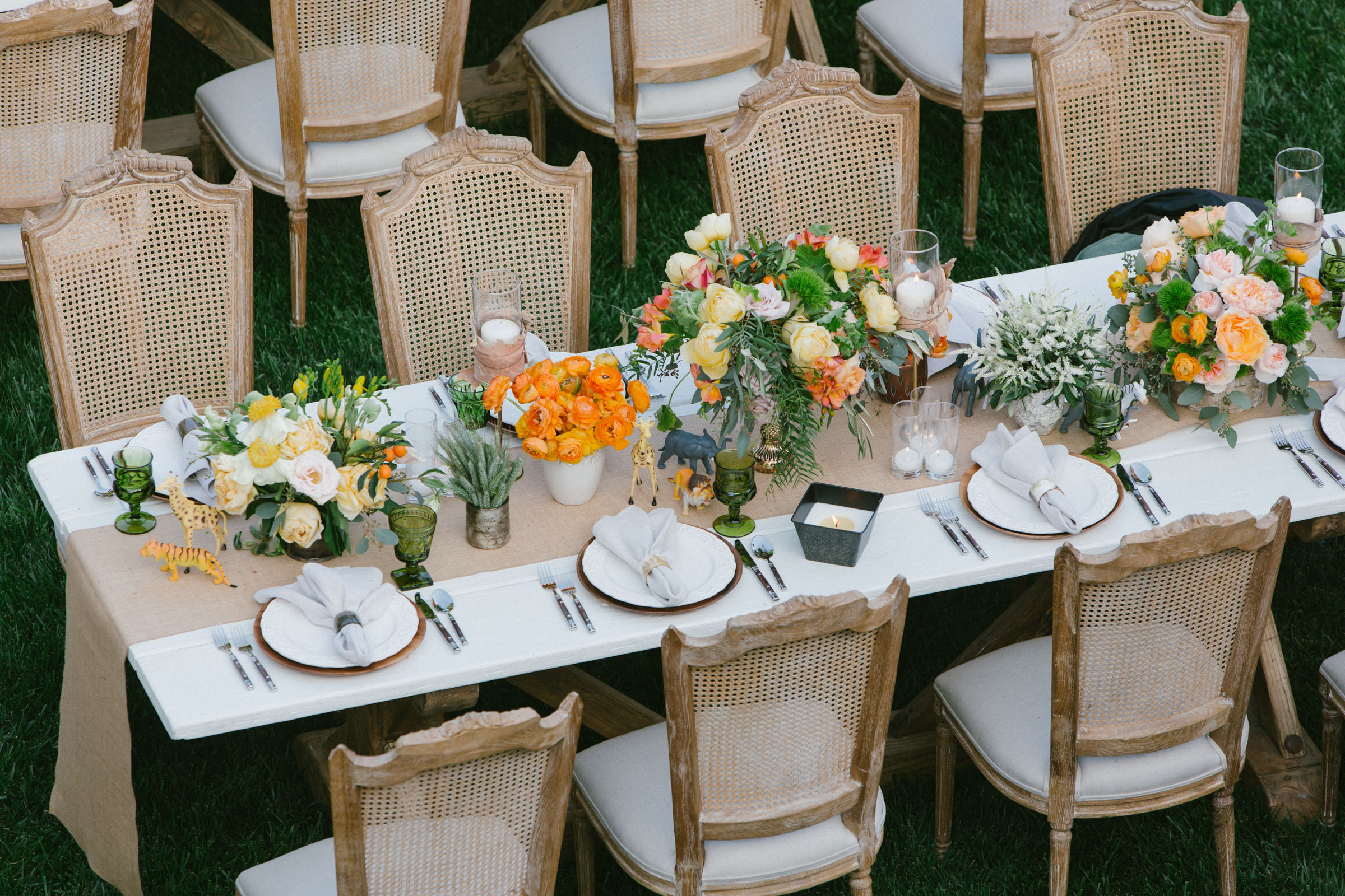 cane back chairs and taupe table runner with flower centerpieces - photo by Amy and Stuart Photography