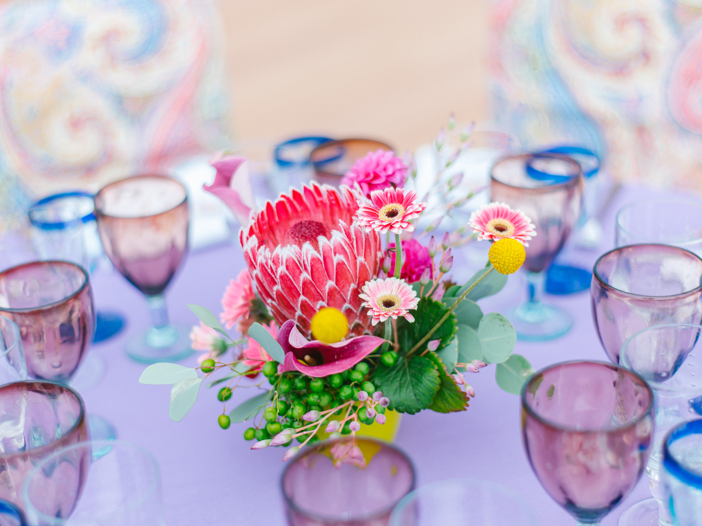 Colorful floral centerpiece with colorful glassware - photo by Amy and Stuart Photography