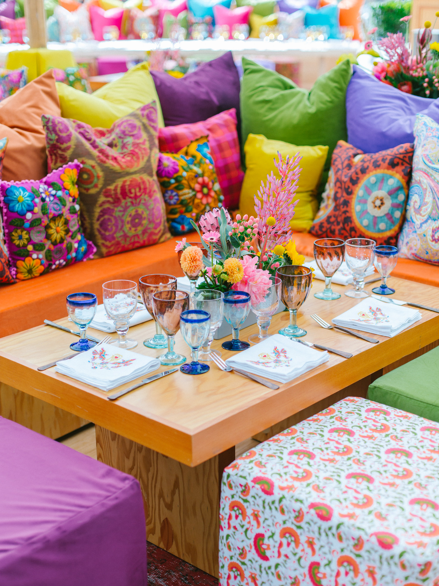 Colorful table against colorful cushions - photo by Amy and Stuart Photography