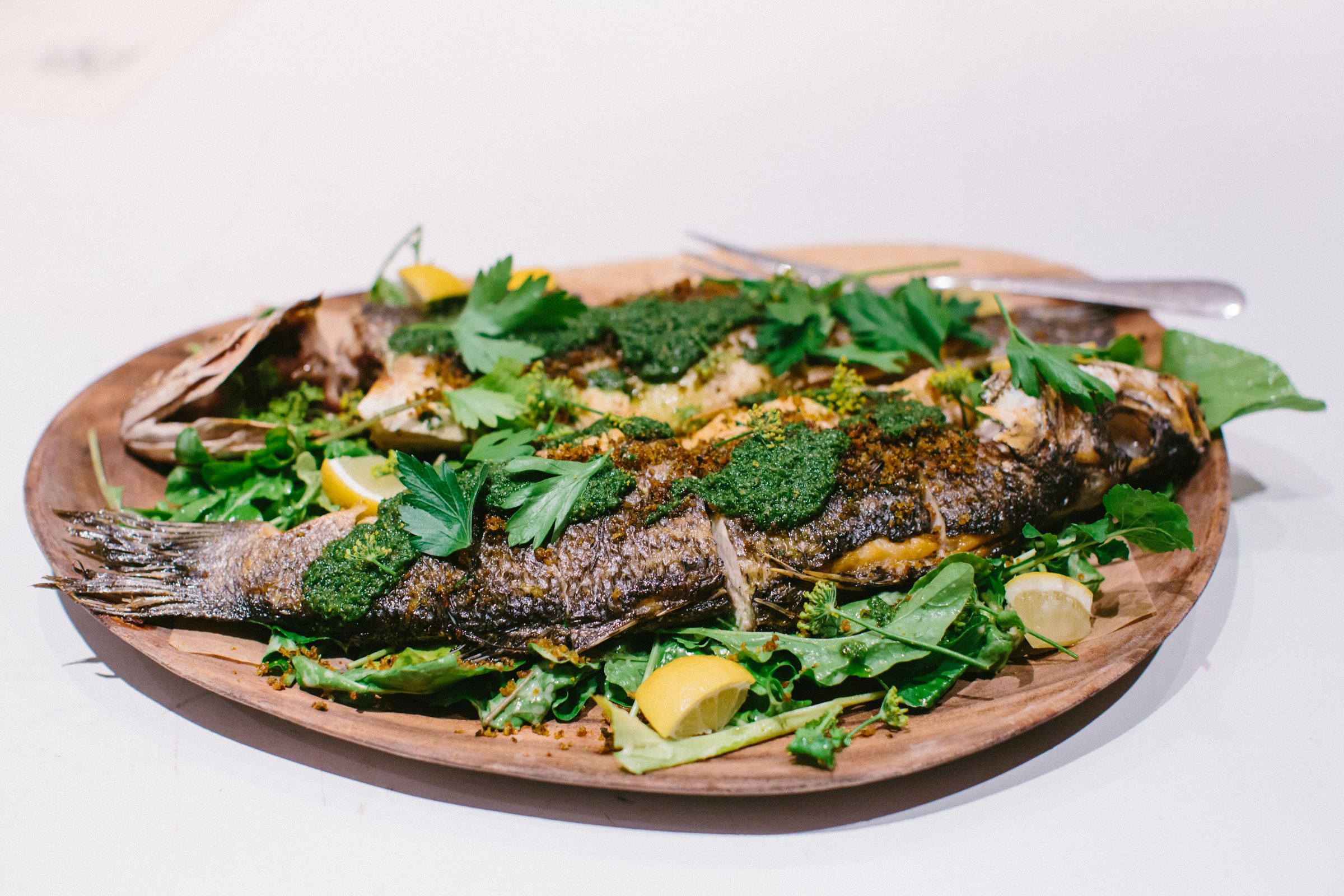 crusted whole fish with herbs on a bamboo plate wedding meal photo- photo by Amy and Stuart Photography, Los Angeles