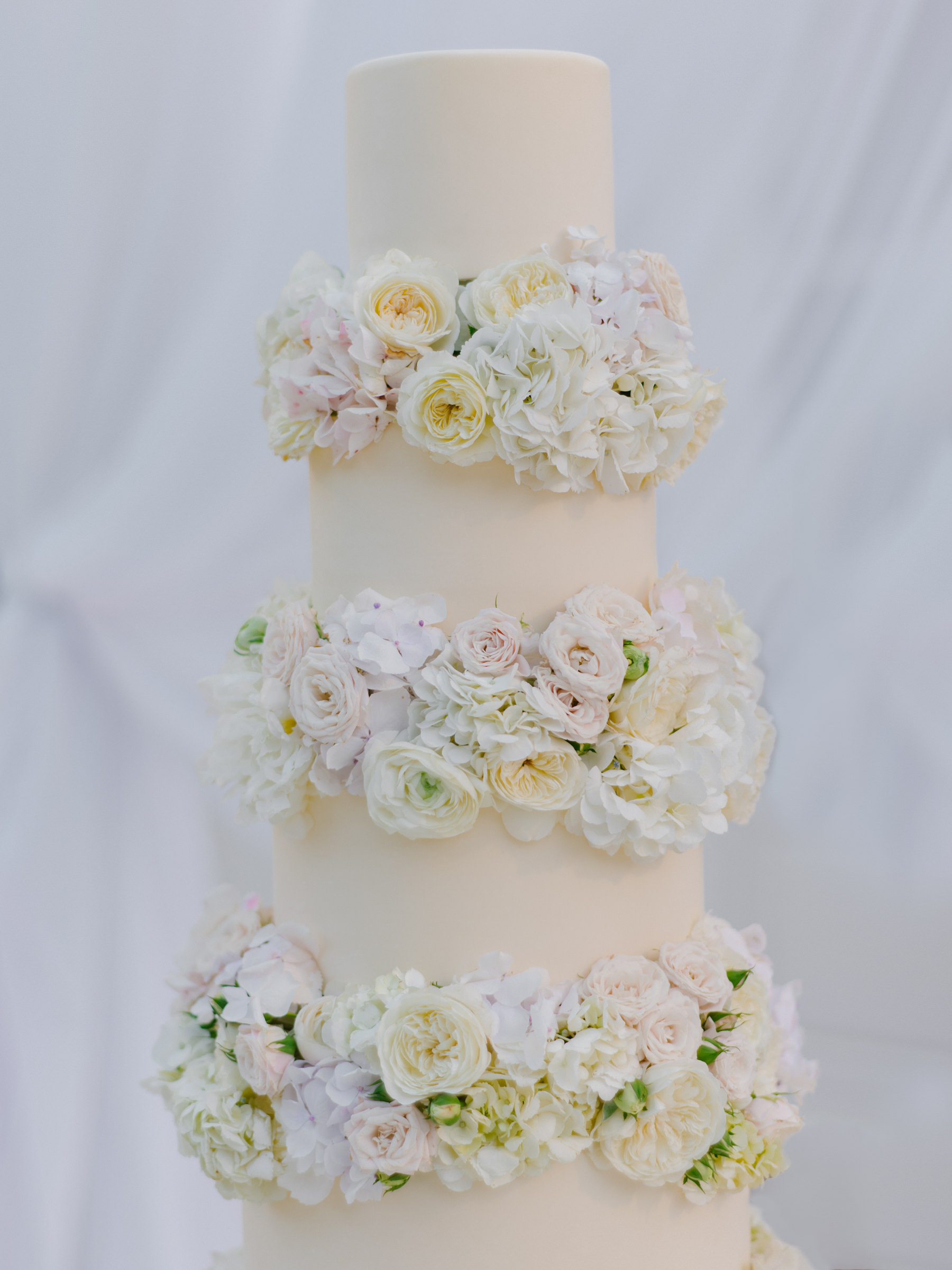 Fondant wedding cake with white, yellow, and pink rose - photo by Amy and Stuart Photography