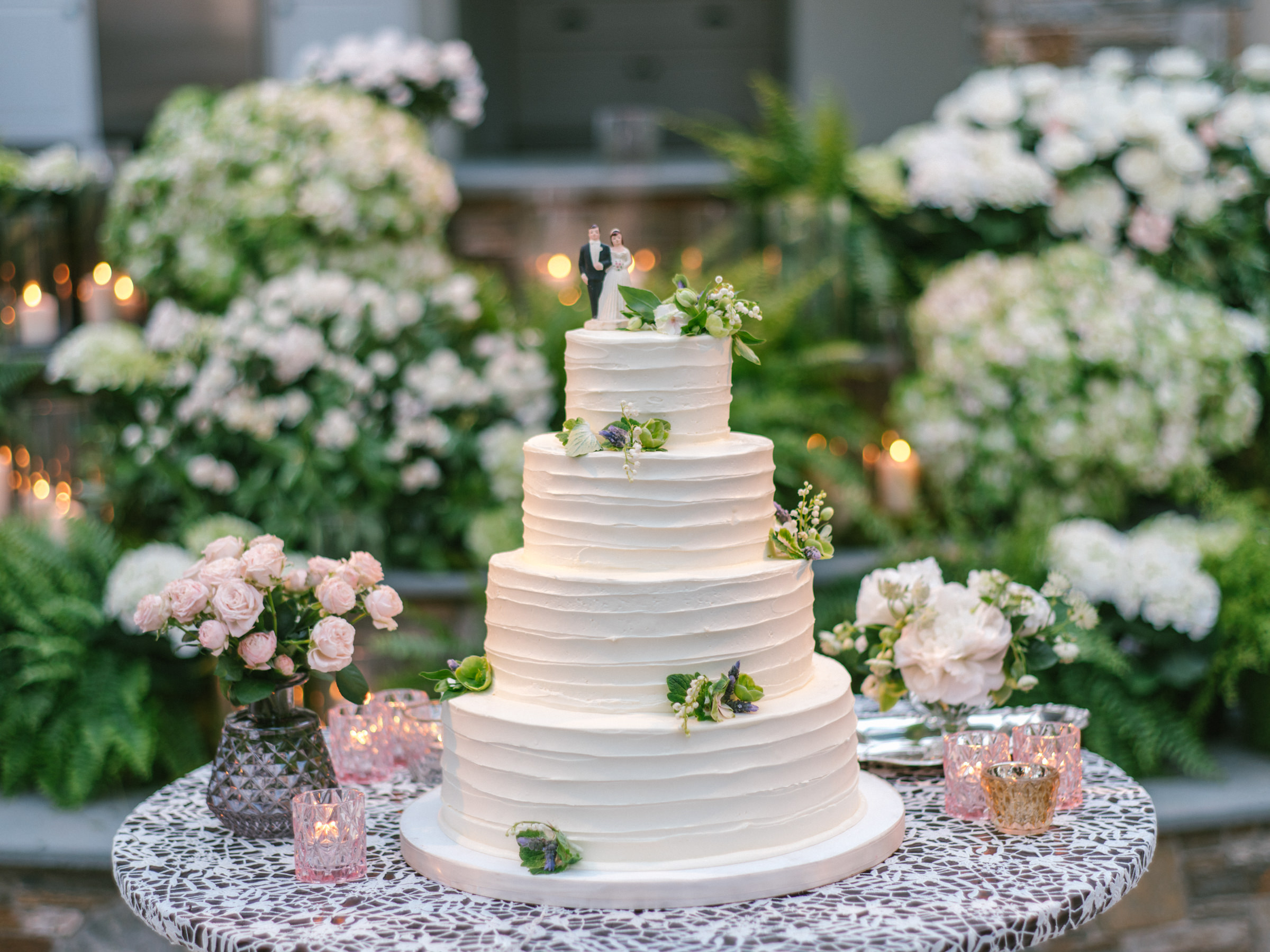 Four tier wedding cake with floral decorations and bride and groom ornament - photo by Amy and Stuart Photography