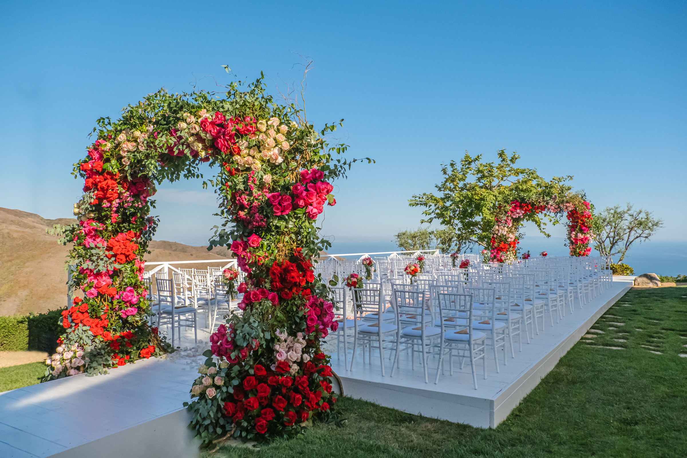 Lush arbor ceremony decor in red green and blush - photo by Amy and Stuart Photography