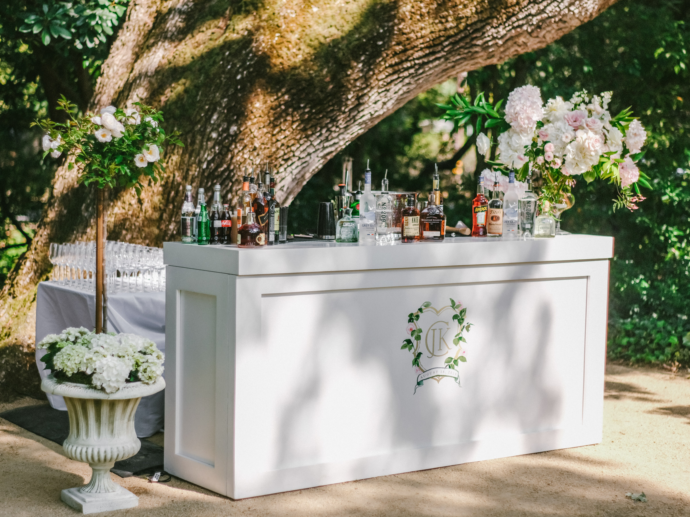 Outdoor bar with monogram beside ancient tree - photo by Amy and Stuart Photography