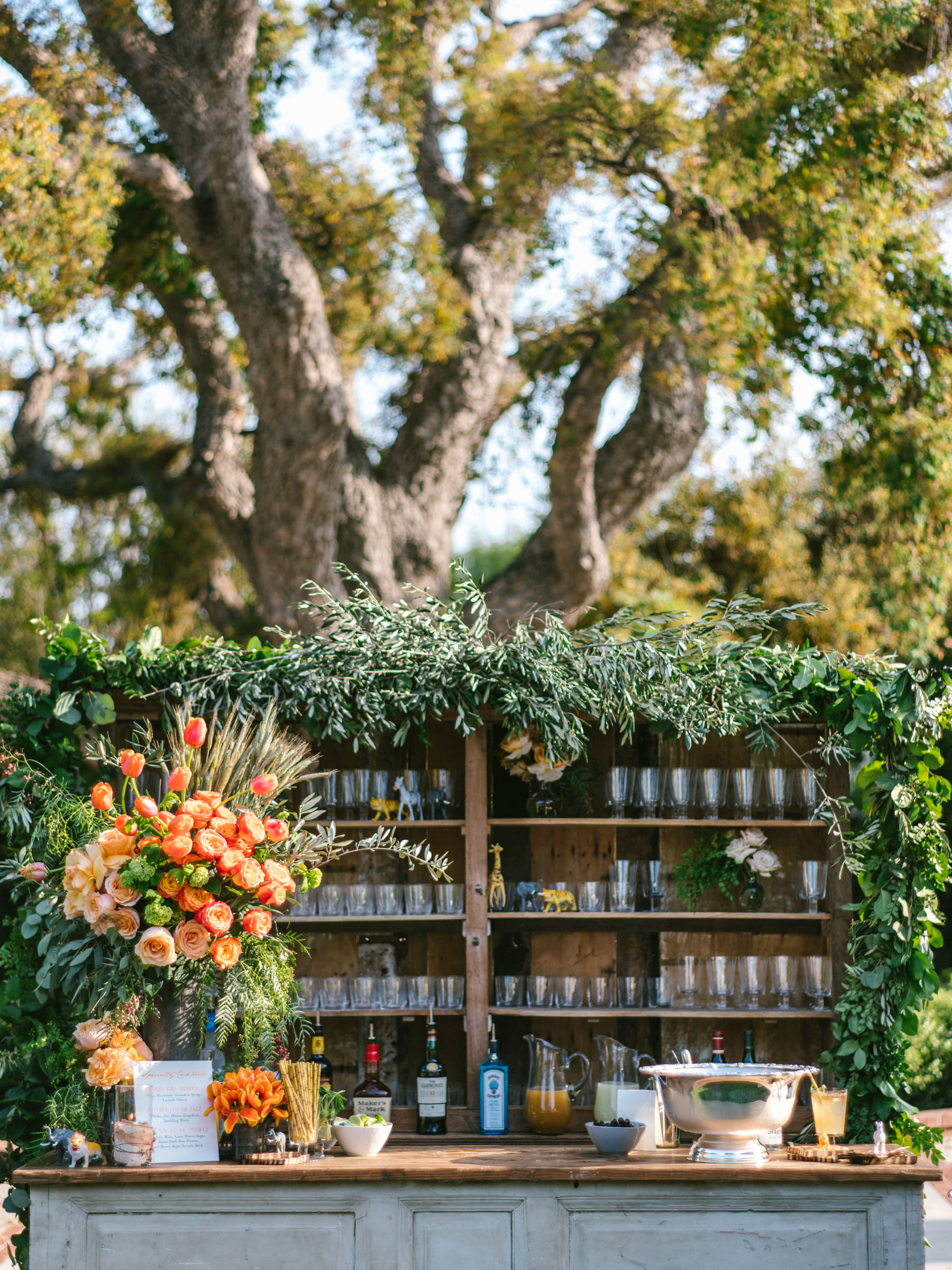 Outdoor reception bar with vines and large tulip display against ancient tree - photo by Amy and Stuart Photography