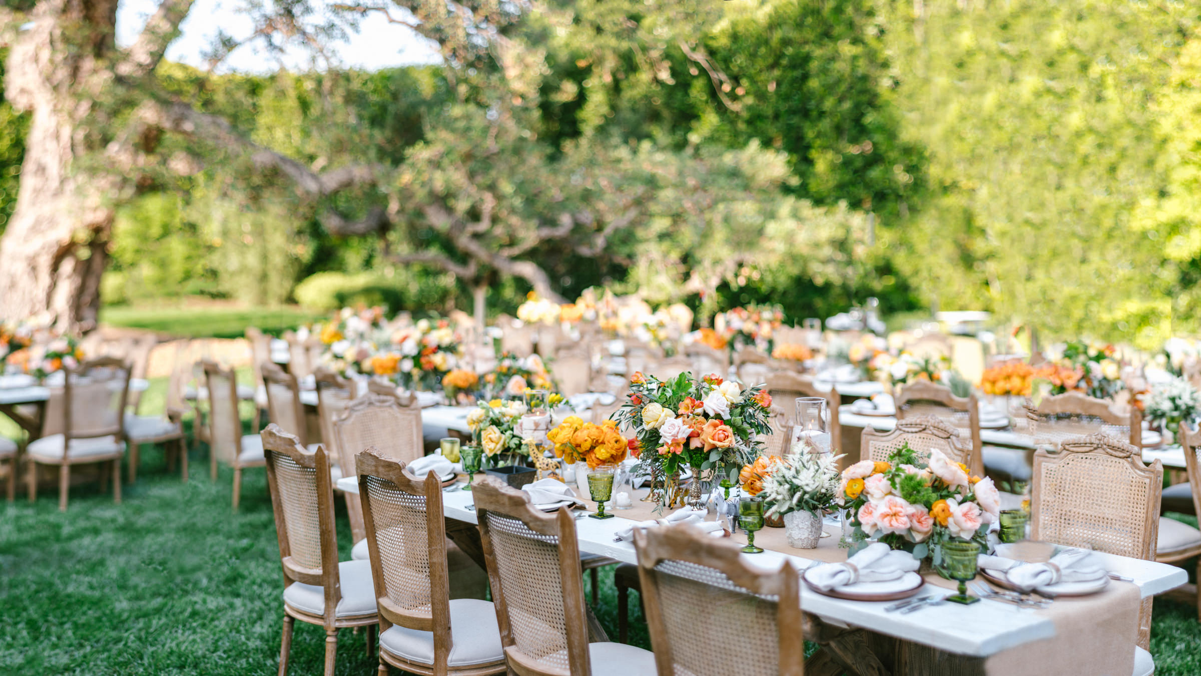 outdoor reception seating with orange floral arrangements- photo by Amy and Stuart Photography