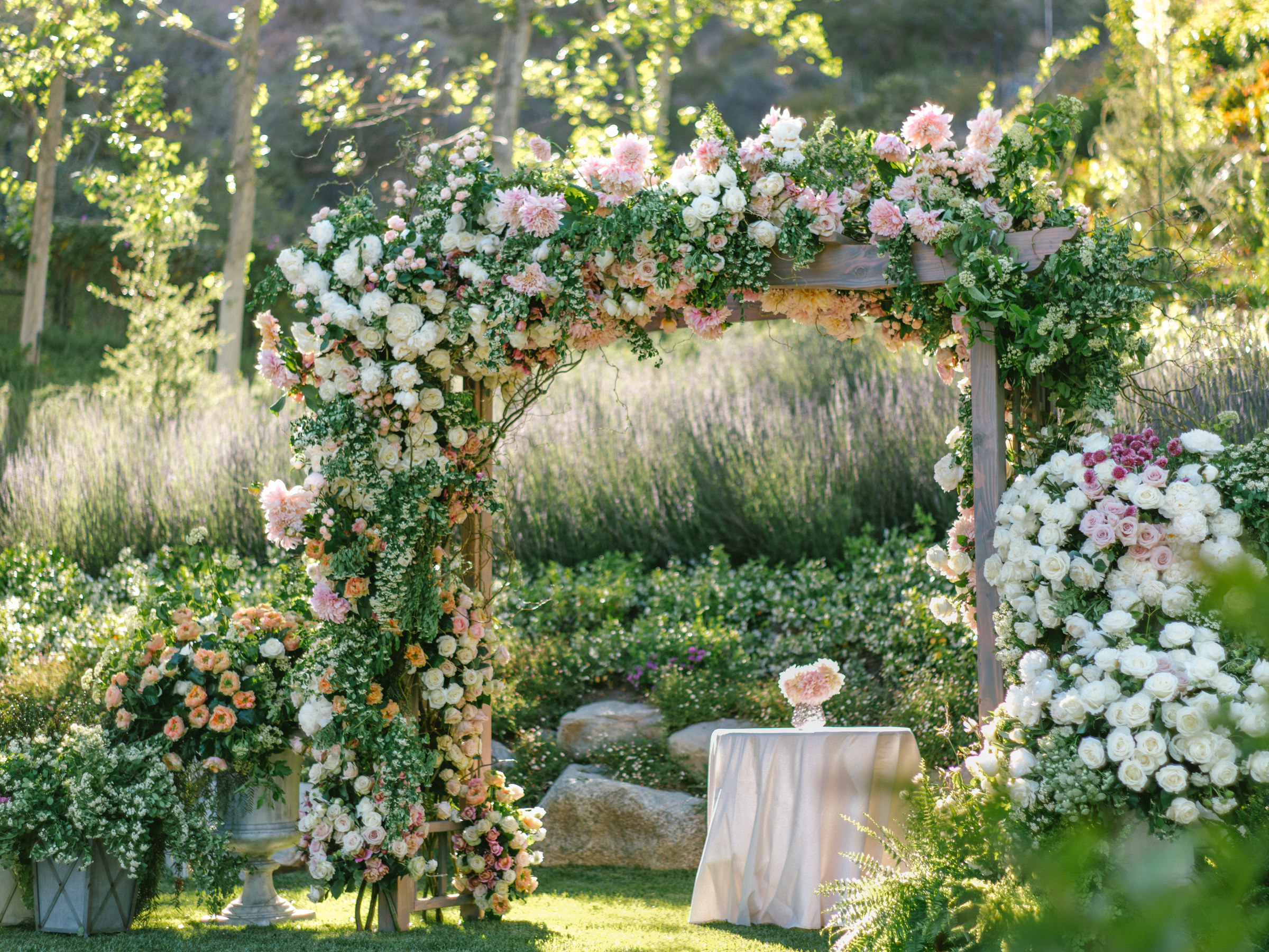 pink and white flower arbor against grasses - photo by Amy and Stuart Photography