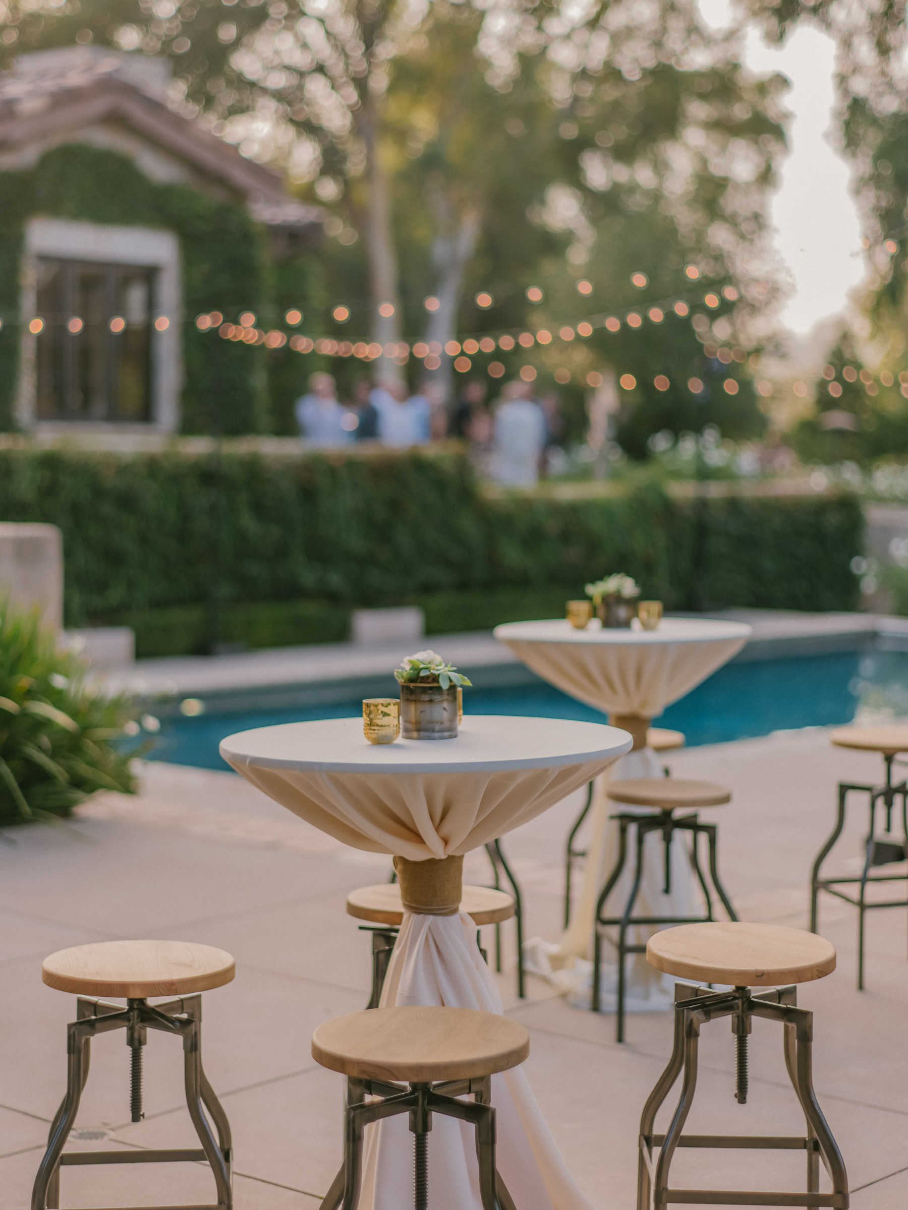 Poolside reception decor with wrapped tables and strung slights - photo by Amy and Stuart Photography