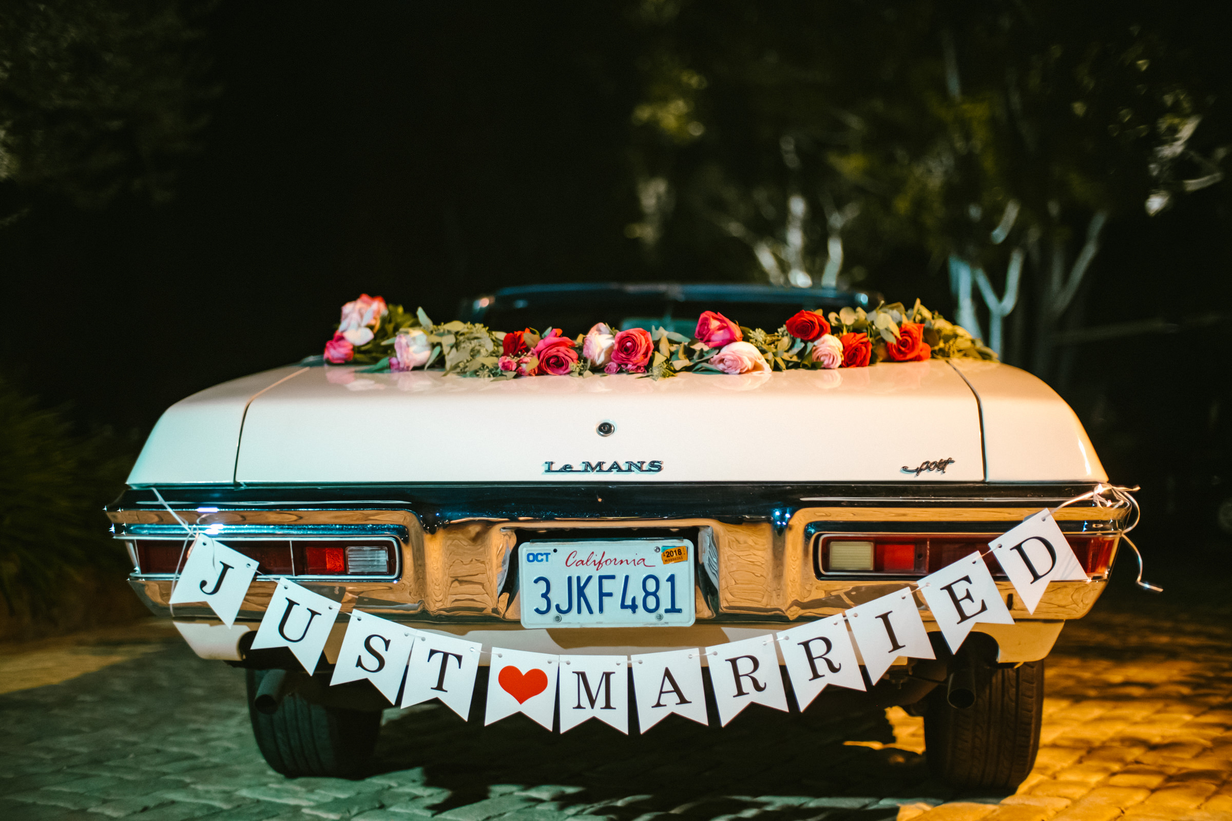 Vintage LeMans convertible with Just Married floral decor - photo by Amy and Stuart Photography
