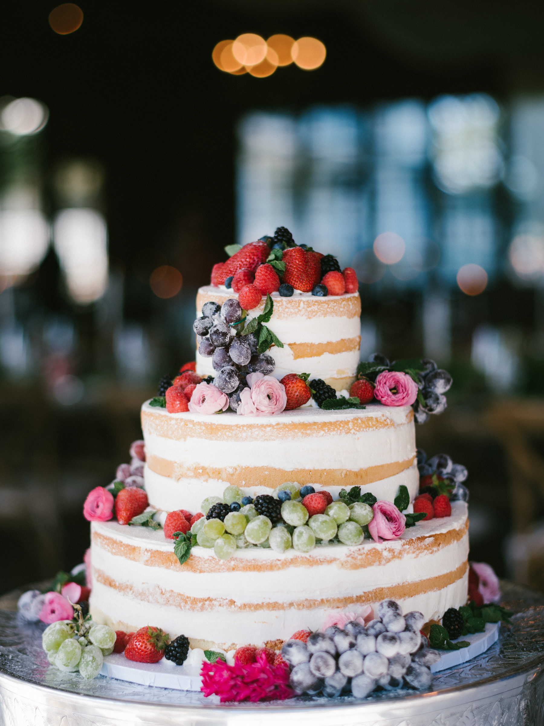 Wedding cake with colorful strawberries, fruits, and flowers - photo by Amy and Stuart Photography