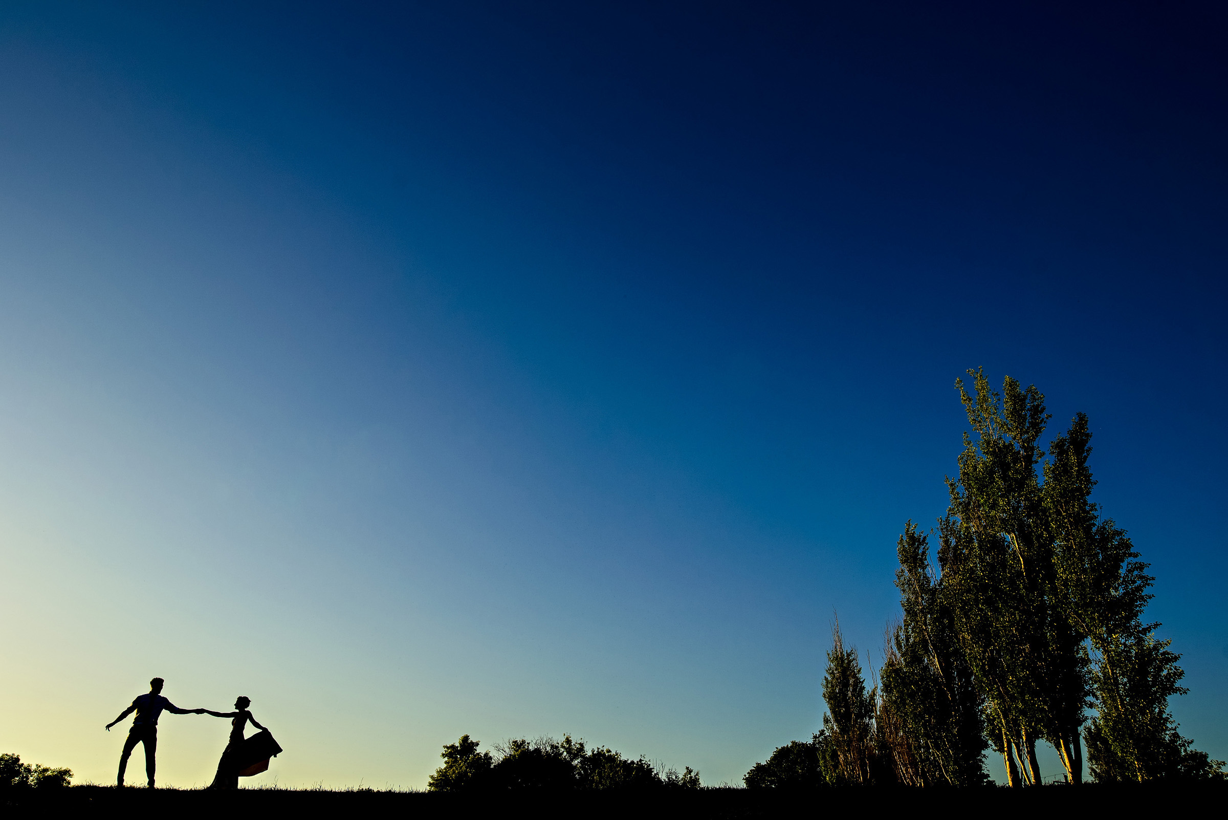 Couple silhouette against blue sky - photo by Moore Photography