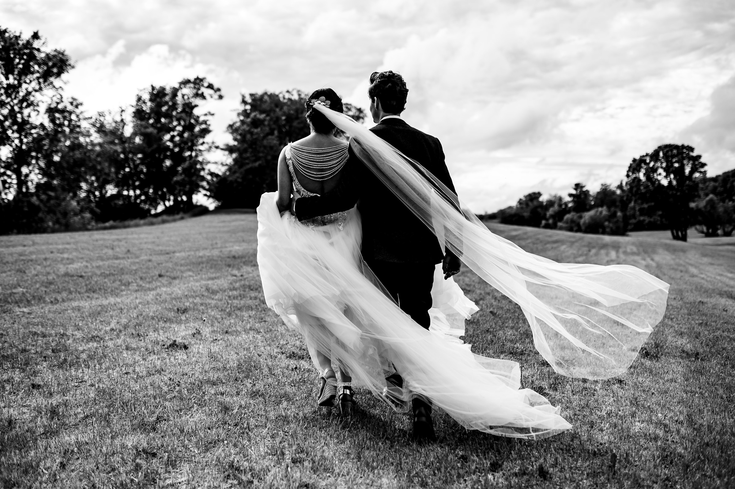 Artistic portrait of couple walking away outdoors - photo by Moore Photography