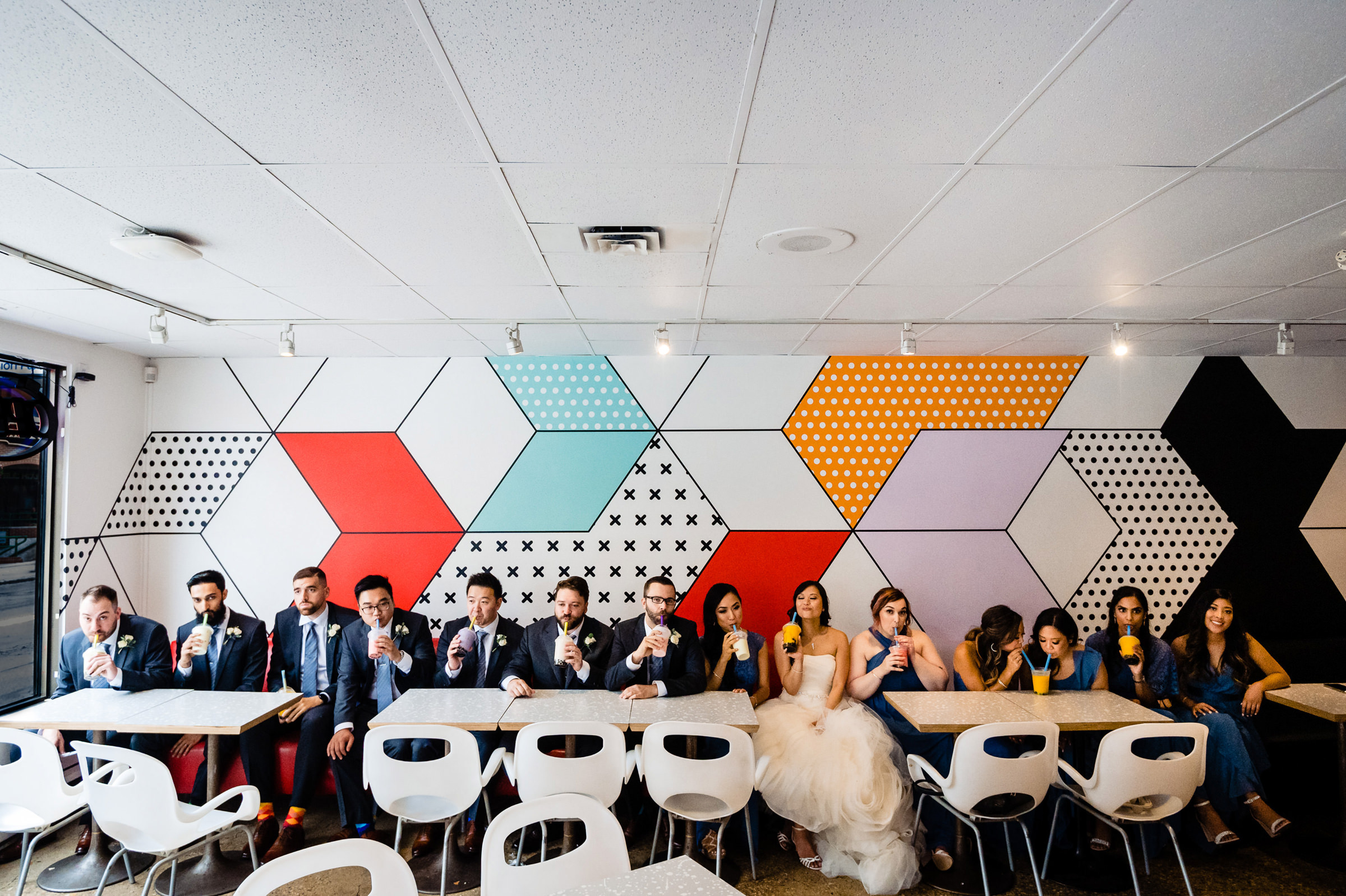 Bridal party at cafe lined up against pop art wall - photo by Moore Photography