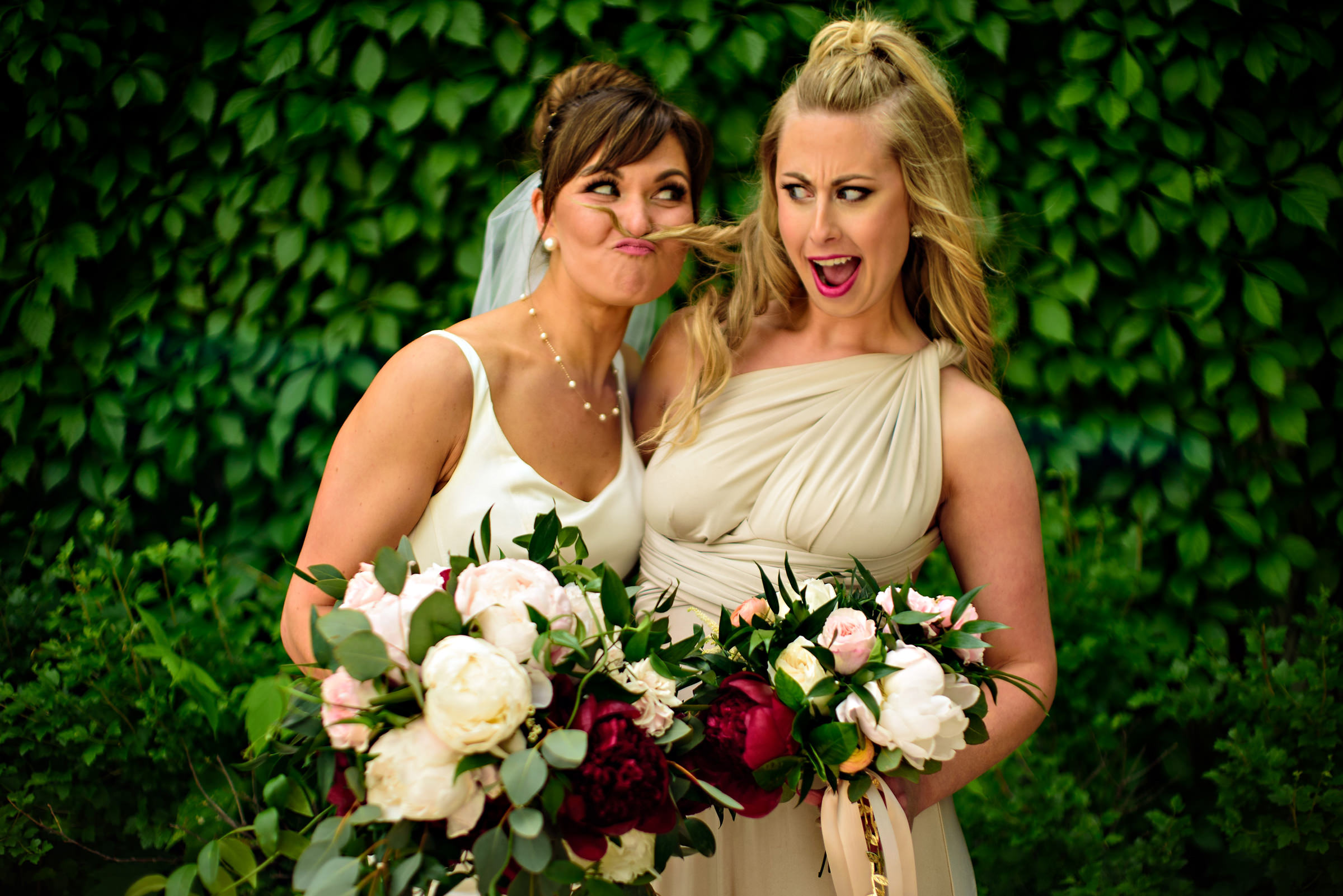 Bride with peony bouquet holds bridesmaid's hair with her nose - photo by Moore Photography