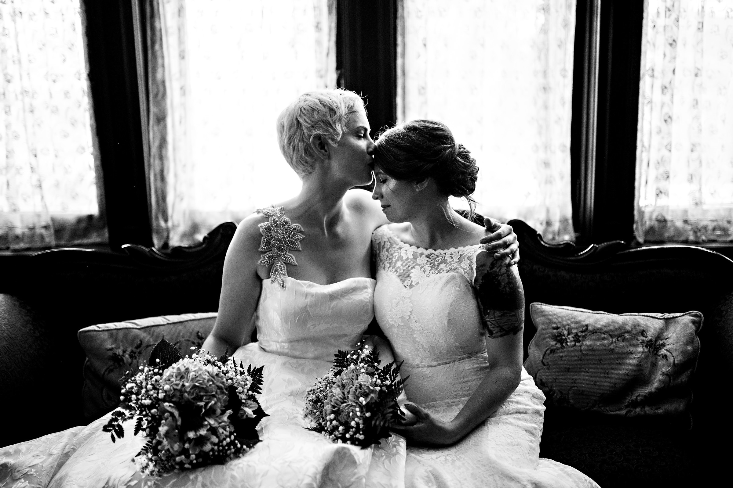 Brides on couch embrace - photo by Moore Photography
