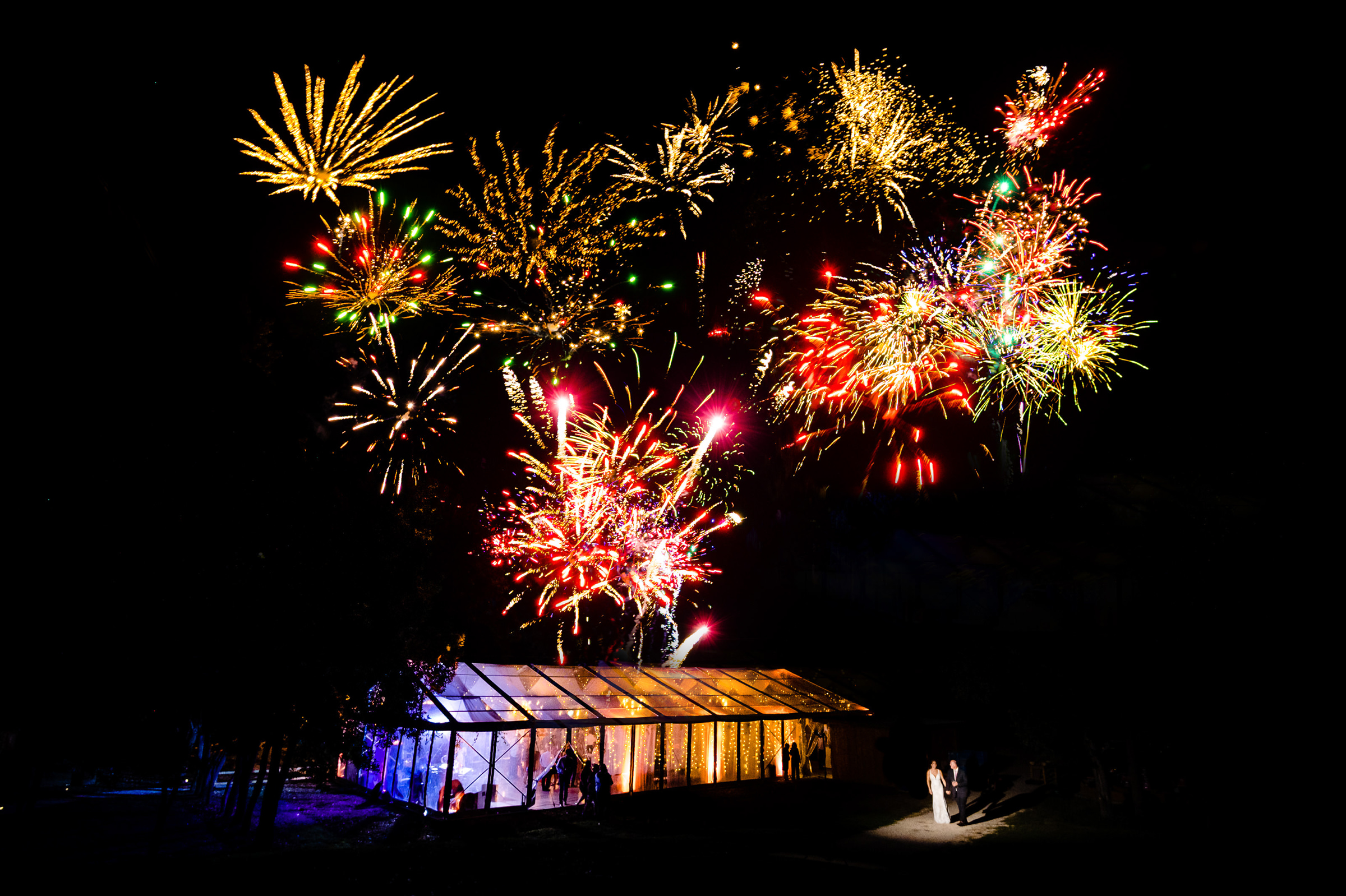 Colorful fireworks over greenhouse with couple in spotlight - photo by Moore Photography
