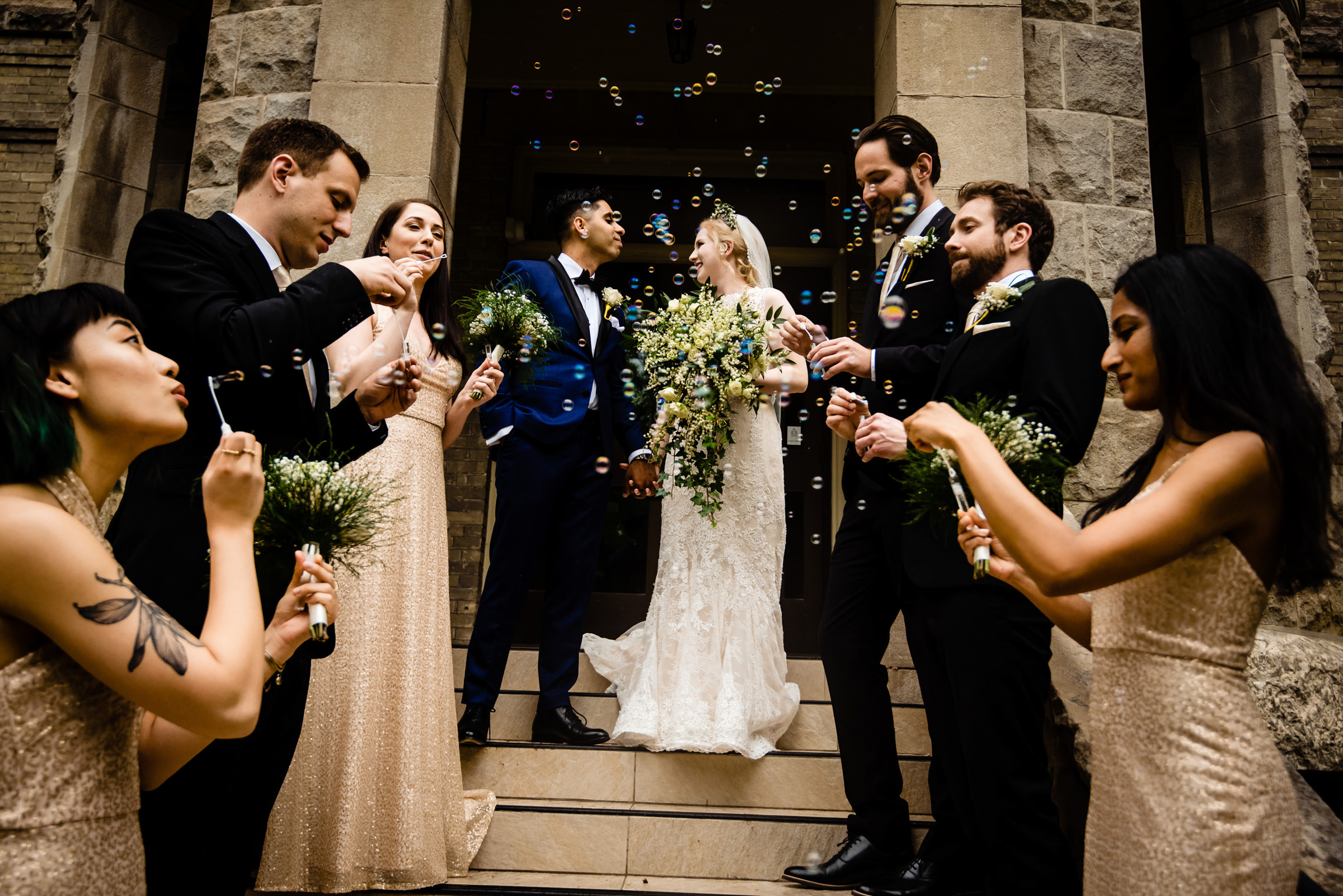 Couple exit church to bubble blowing bridal party - photo by Moore Photography