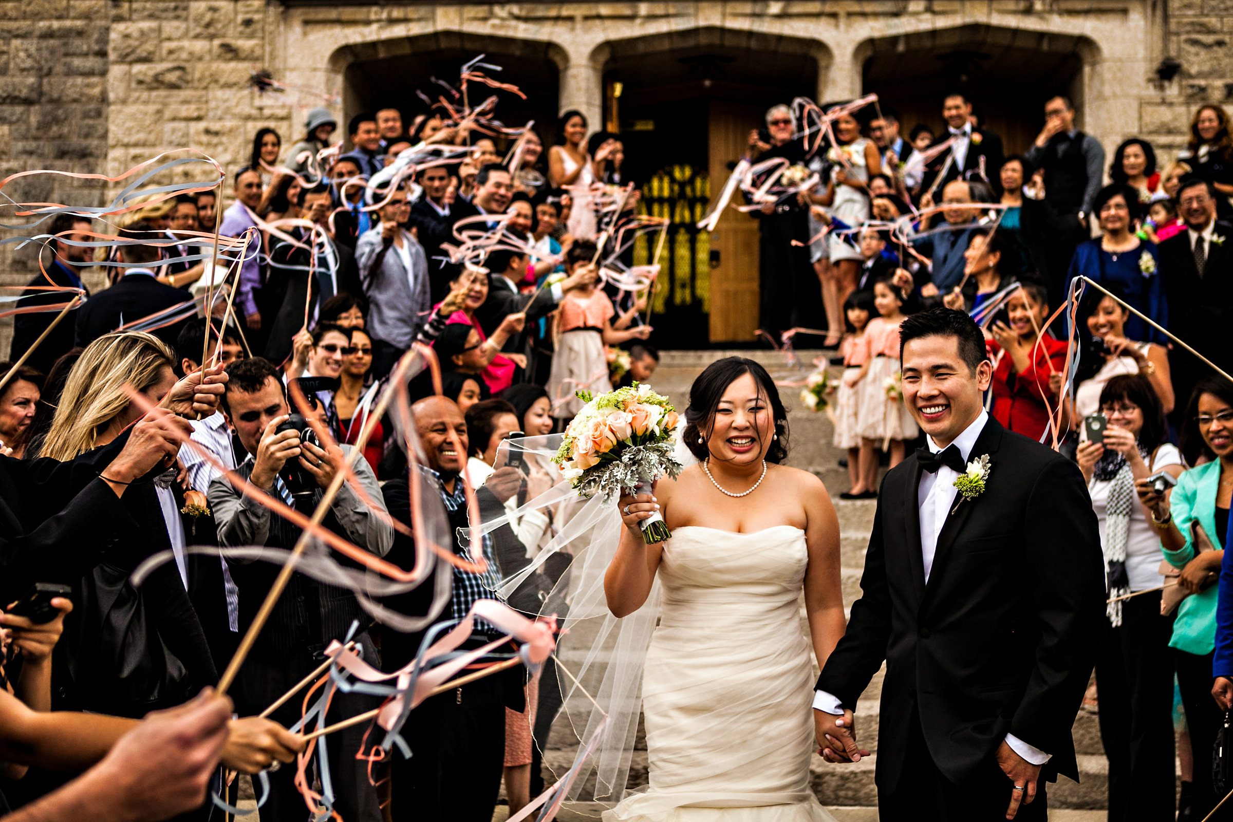 Couple leaves ceremony as guests wave ribbon streamers - photo by Moore Photography
