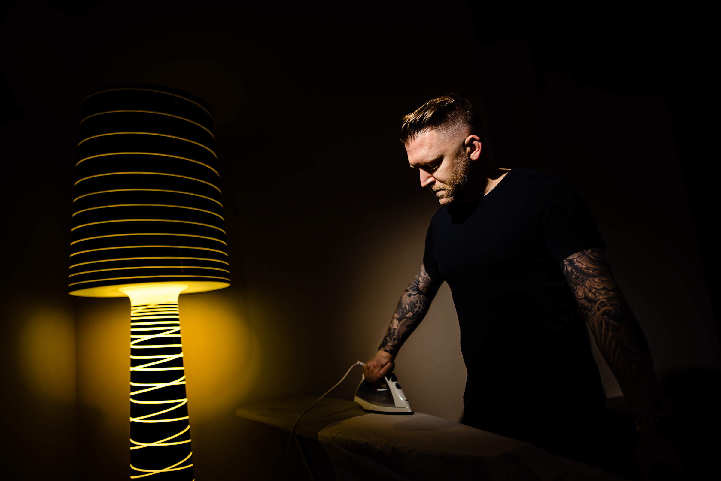Dramatic lighting on man ironing - photo by Moore Photography