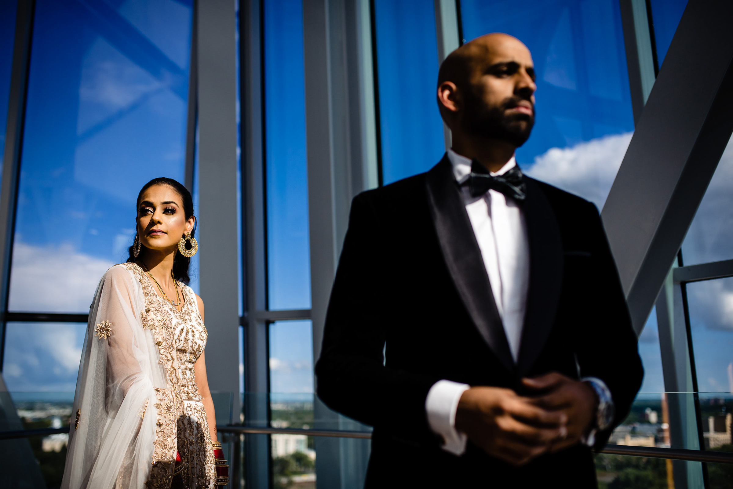 Glamorous bride and groom against interior glass architecture - photo by Moore Photography