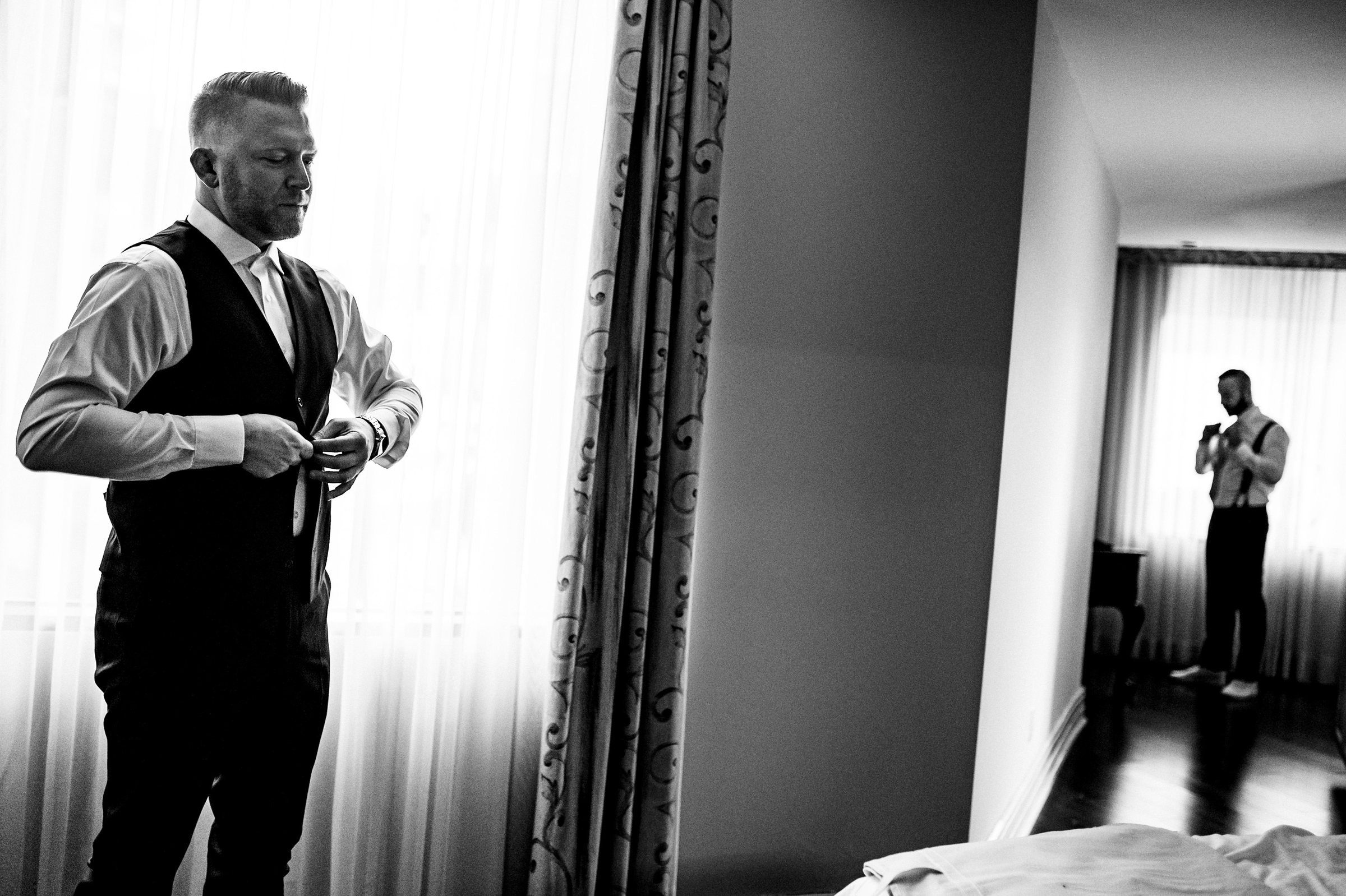 Groom and groomsman getting dressed - photo by Moore Photography