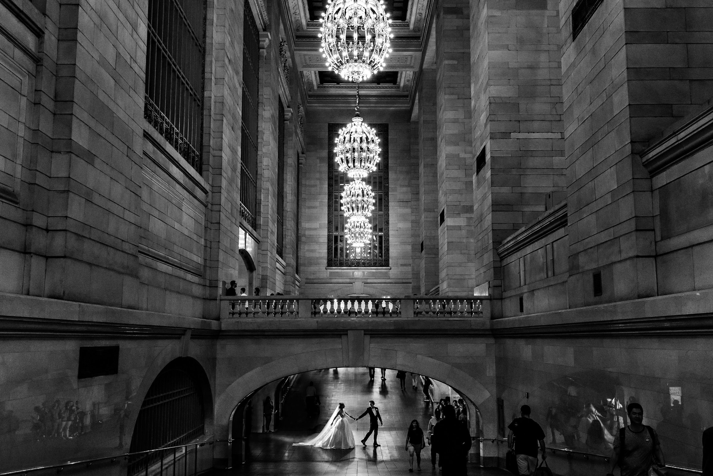 Groom leads bride across hallway lit by chandeliers - photo by Moore Photography