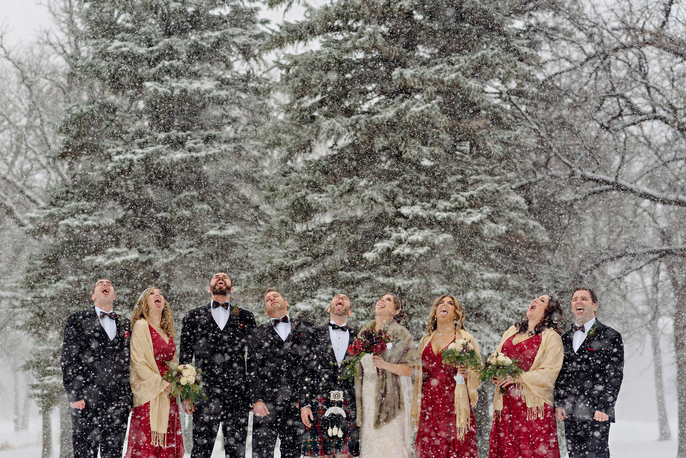 Group portrait of bridal party putting their tounges out in the snow - photo by Moore Photography