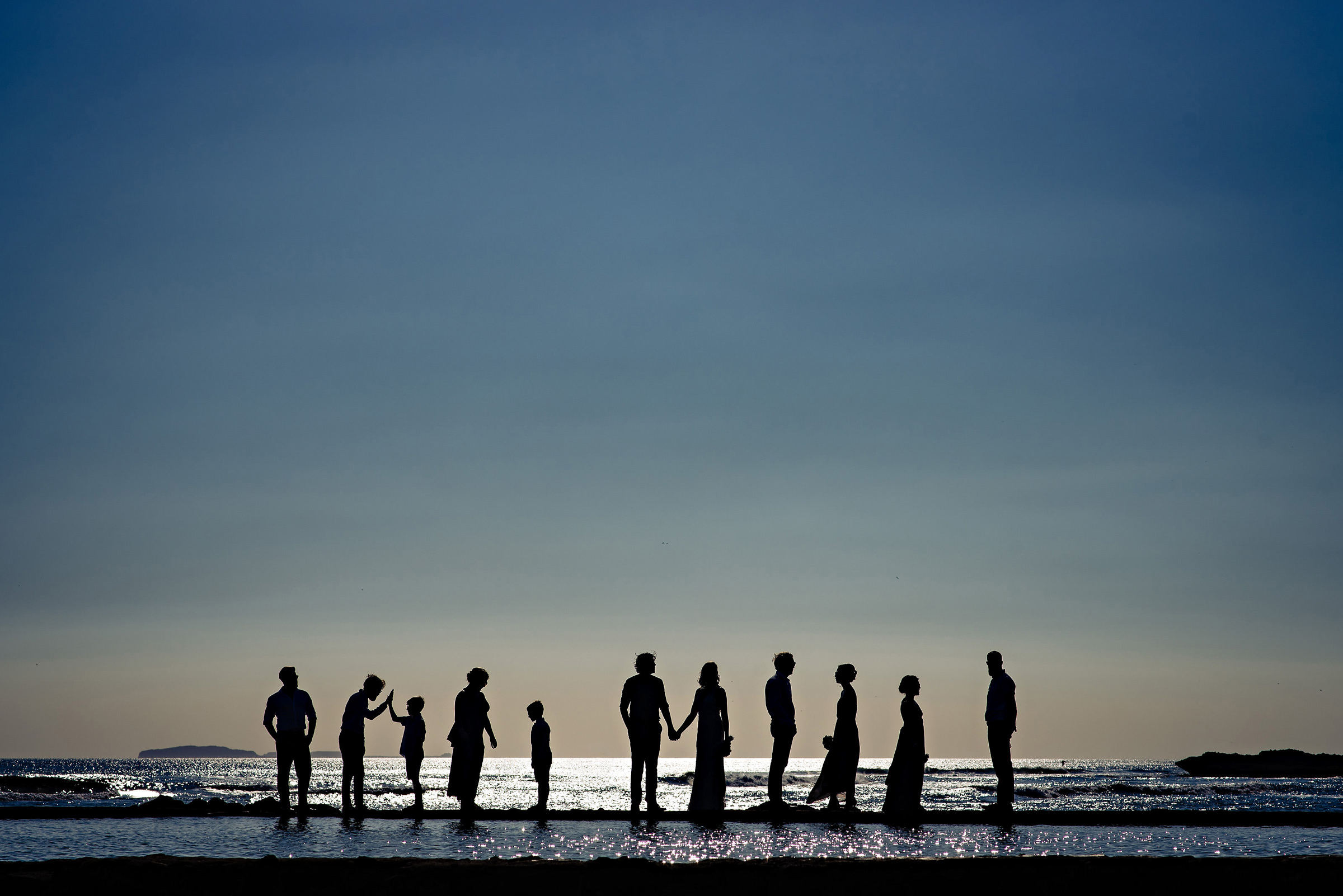 Group shot silhouette at surfs edge - photo by Moore Photography