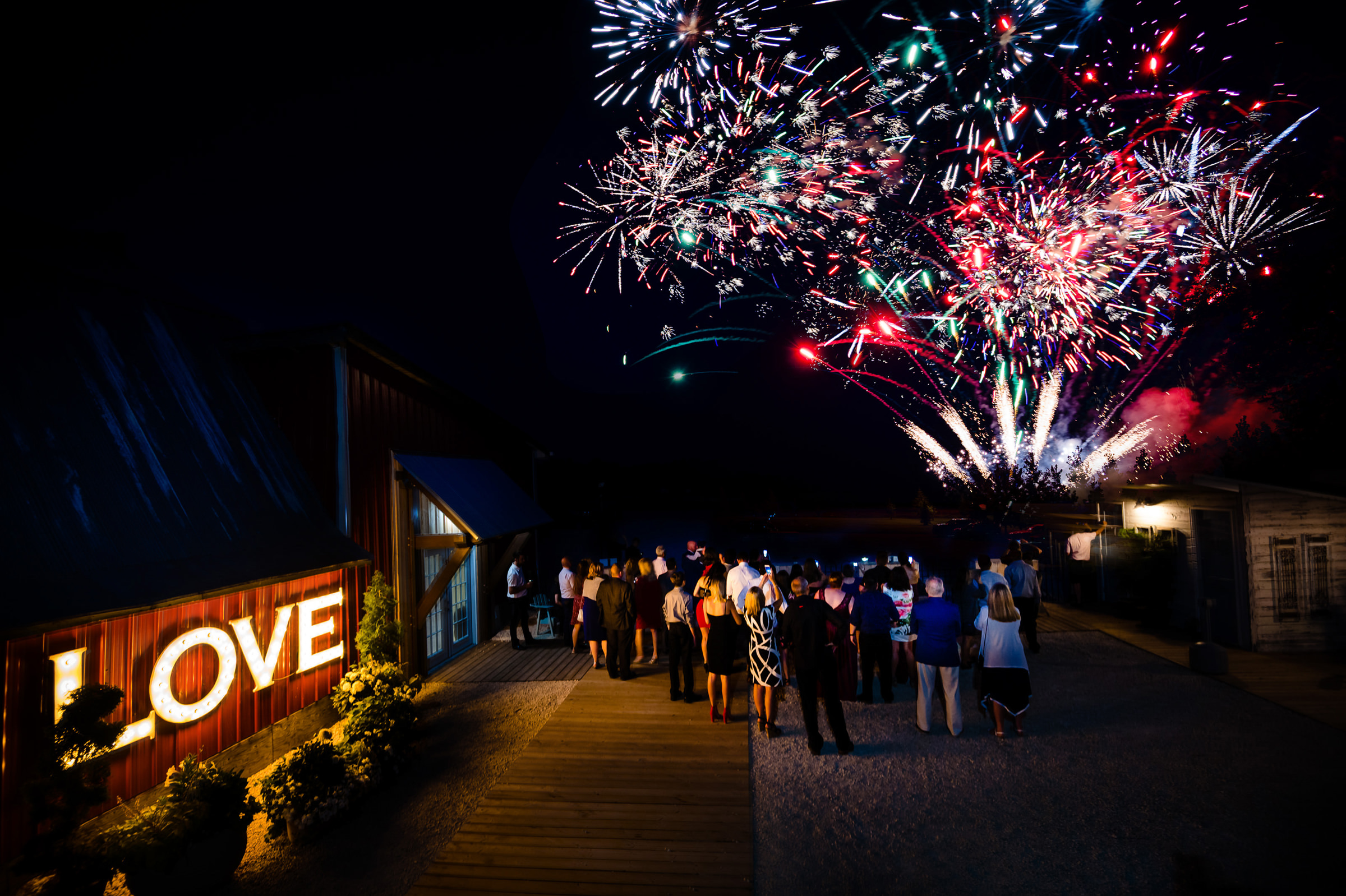 Guests gather for fireworks with love sign in background - photo by Moore Photography
